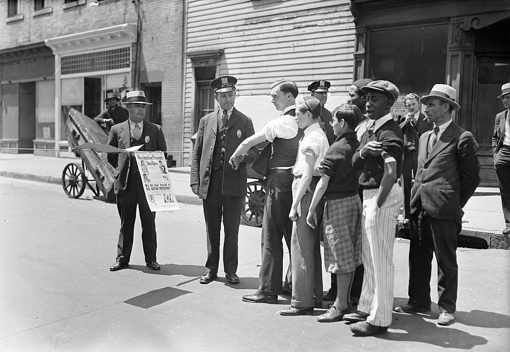 Health officer Jones questions persons before permitting them to pass the quarantine barriers that have been placed at Barclay Street in Newark, N.J., in 1931 to check the spread of smallpox. All entering or leaving must show a vaccination not more than five days old.