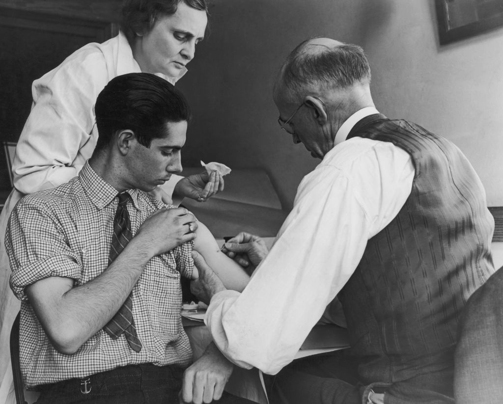 A teenage boy is vaccinated against smallpox by a school doctor and a county health nurse, Gasport, N.Y., March 15, 1938.