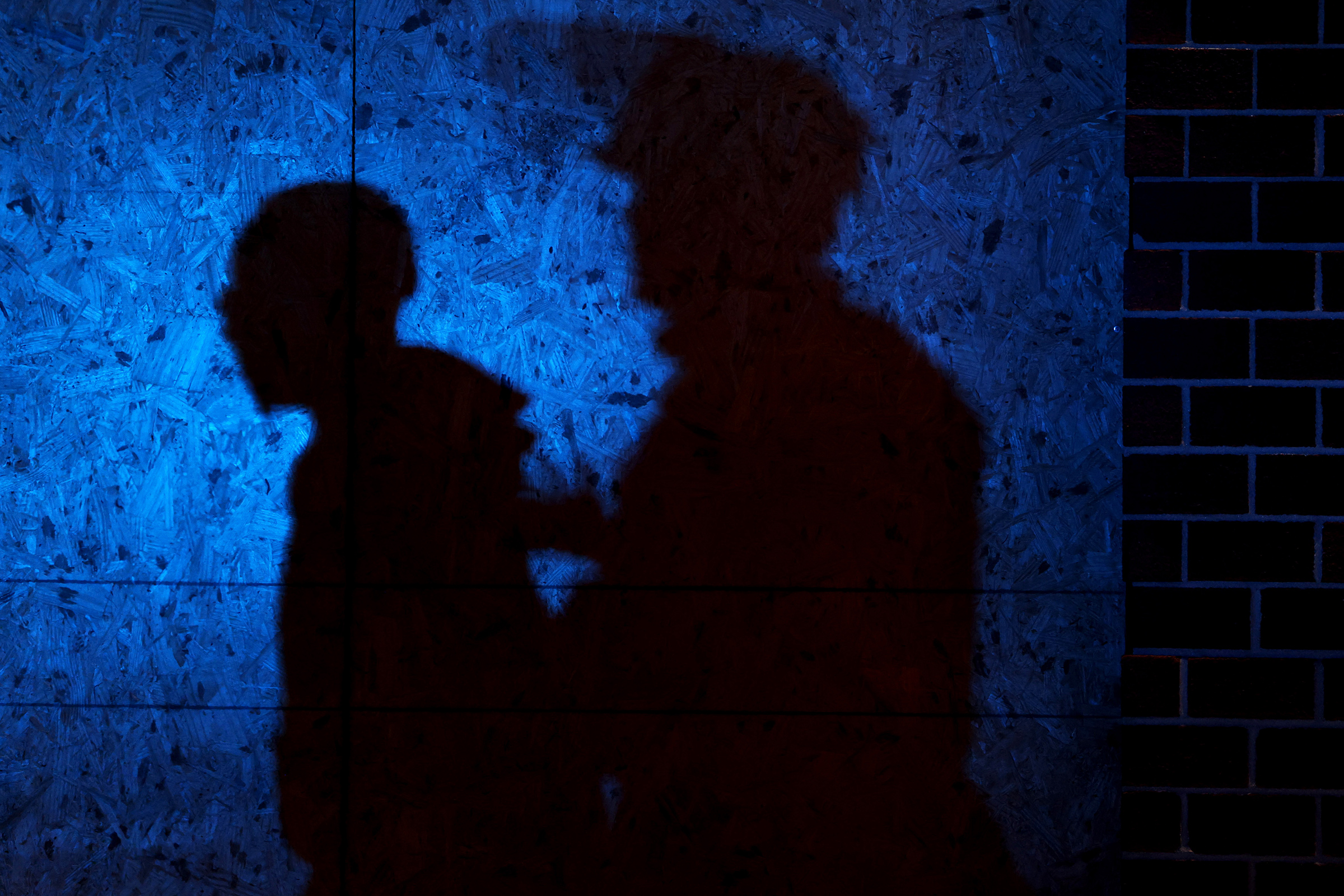 The shadow of a Louisville Police officers arresting a demonstrator is seen on a wall on September 23, 2020 in Louisville, Kentucky. A Kentucky grand jury indicted one police officer involved in the shooting of Breonna Taylor with three counts of wanton endangerment.