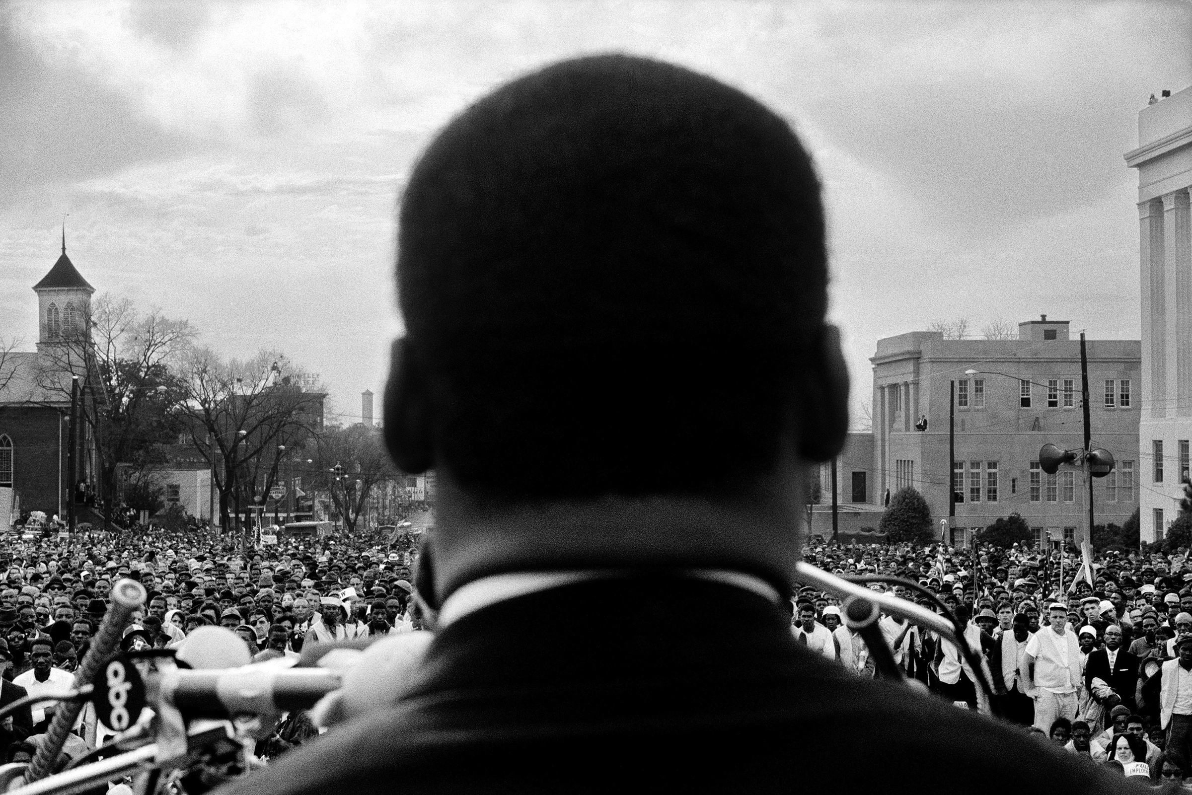 Dr. Martin Luther King, Jr. seen close from the rear, speaking to 25,000 civil rights marchers in front of the Alabama state capital building, at the conclusion of the Selma to Montgomery march, Montgomery, Alabama, March 25, 1965.