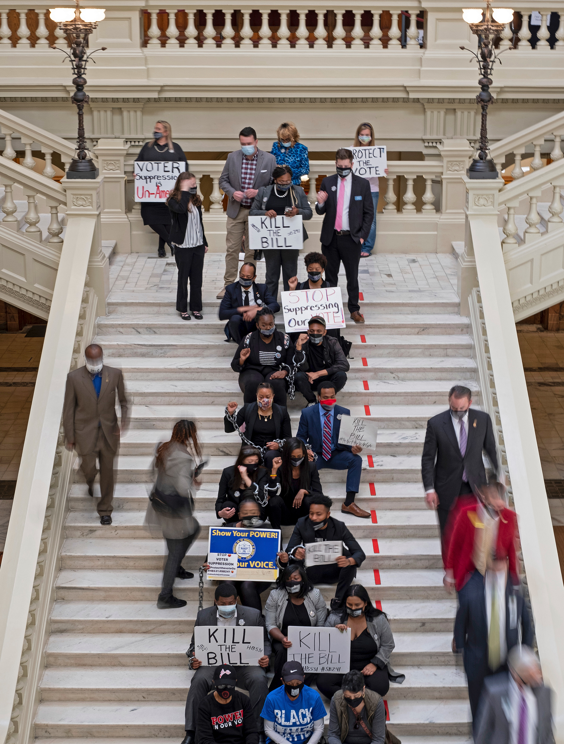 Protesters opposed to changes in Georgia's voting laws sit on the steps inside the State Capitol in Atlanta, Ga., as the Legislature breaks for lunch Monday, March 8, 2021, in Atlanta.