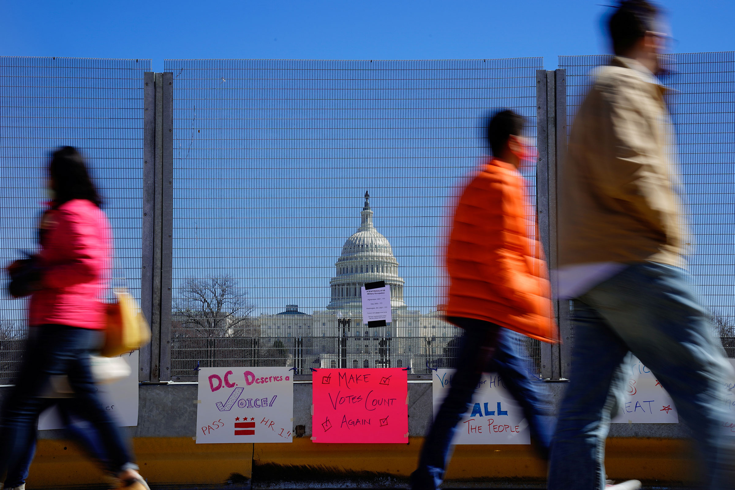 People walk past signs hung on a security fence in support of expanded voting rights near the Capitol in Washington, on March 7, 2021.