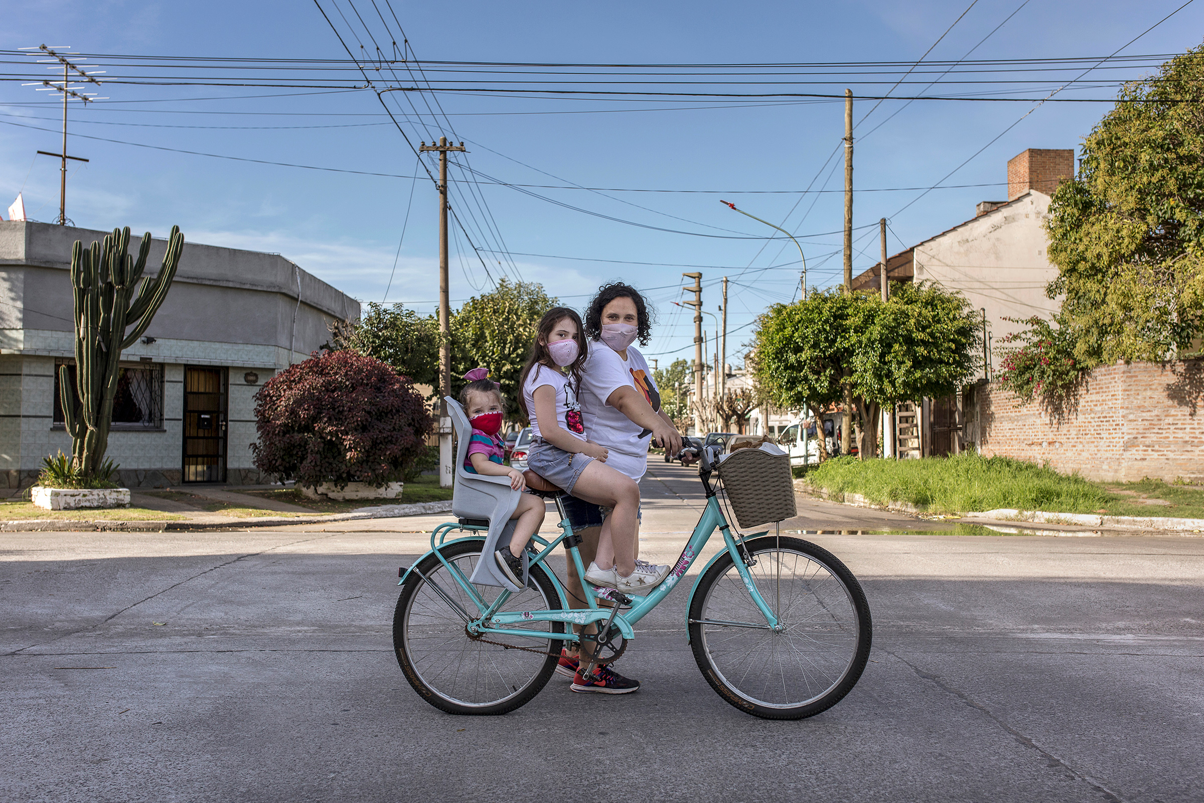 María Teresa Arzamendia stands for a portrait with her two daughters Leia and Catalina and her bicycle with pastries in El Palomar, Buenos Aires Province, on April 17.