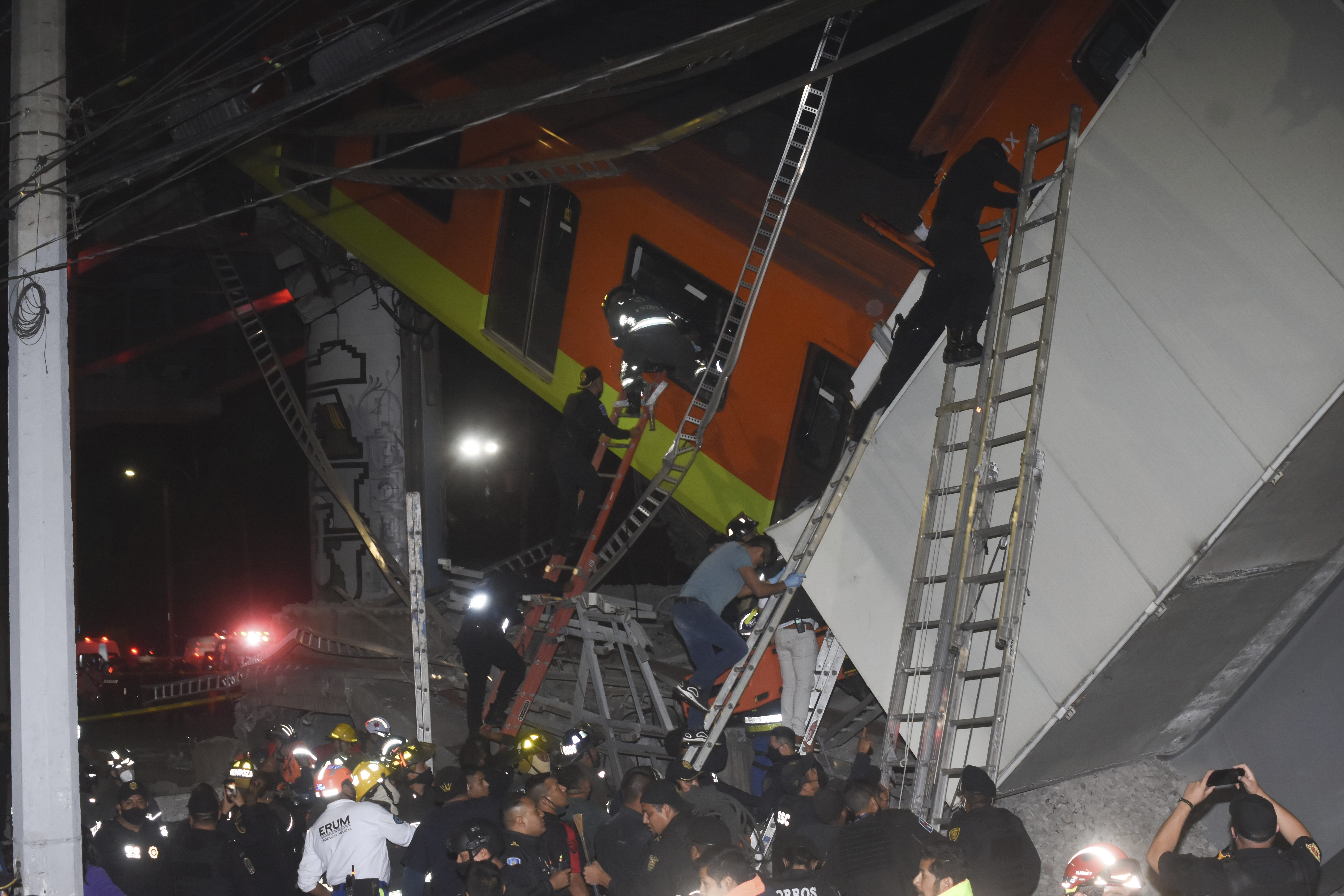 Mexico City fire fighters and rescue personnel work to recover victims from a subway car that fell after a section of Line 12 of the subway collapsed in Mexico City, Monday, May 3, 2021.