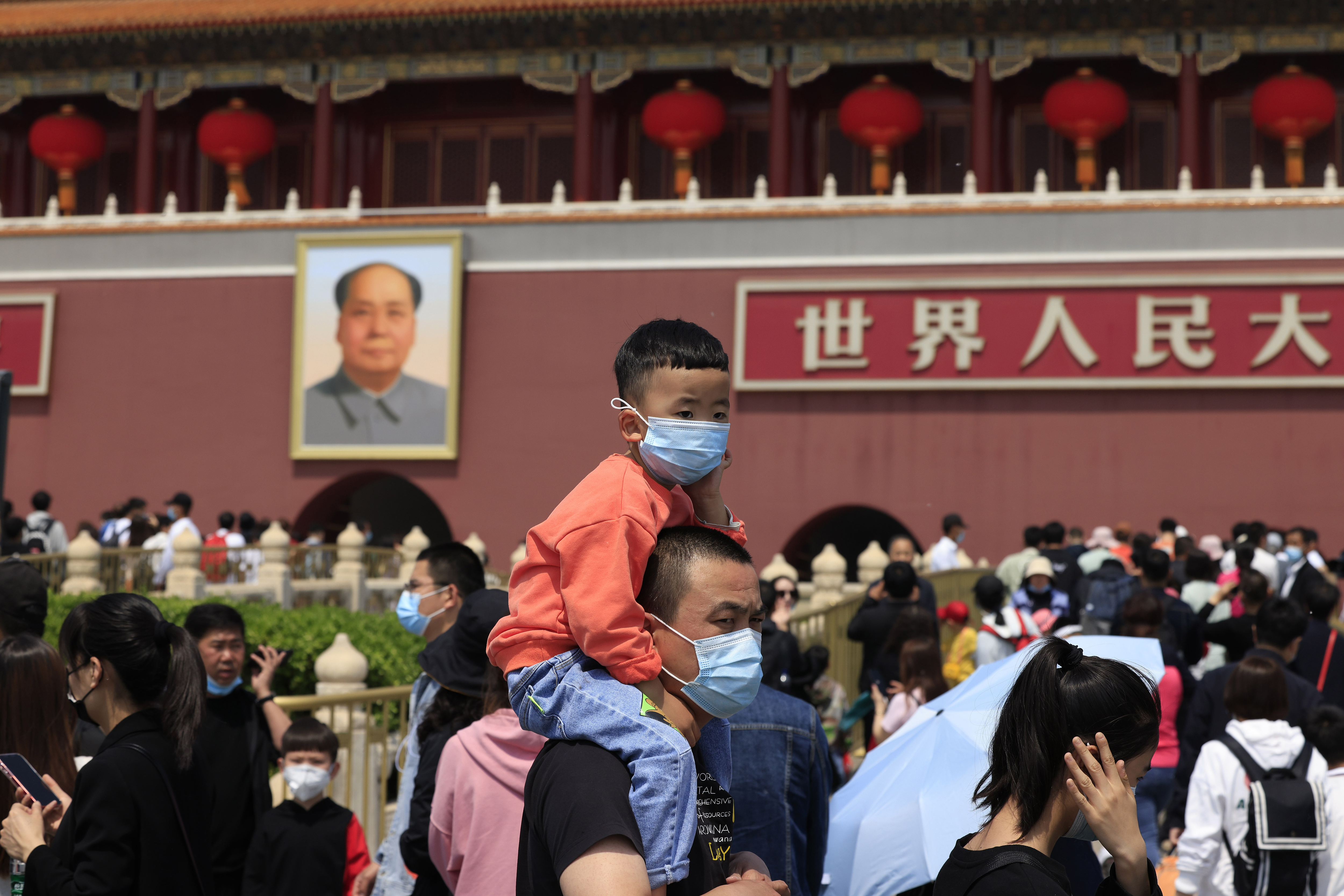 In this May 3 2021 photo, a man and child visit Tiananmen Gate near the portrait of Mao Zedong in Beijing.