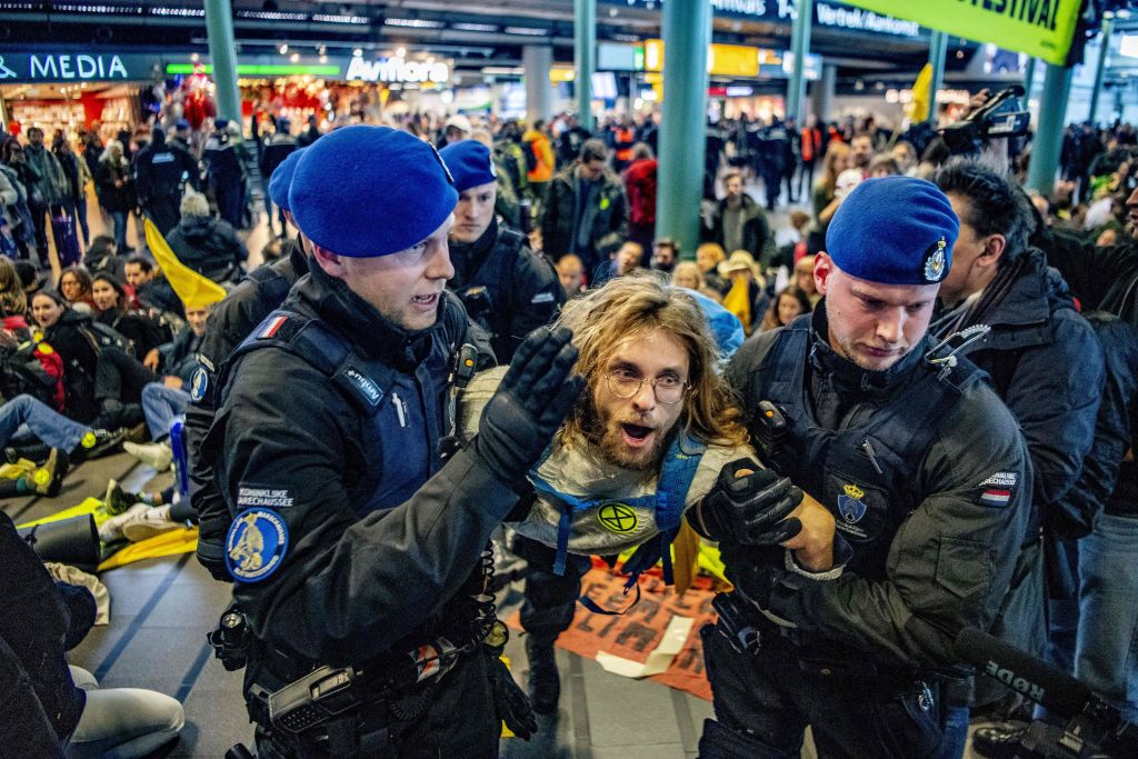 Royal Dutch police officers escort a Greenpeace activist during a protest to denounce airline pollution in the main hall of the Amsterdam Schiphol airport on December 14, 2019.