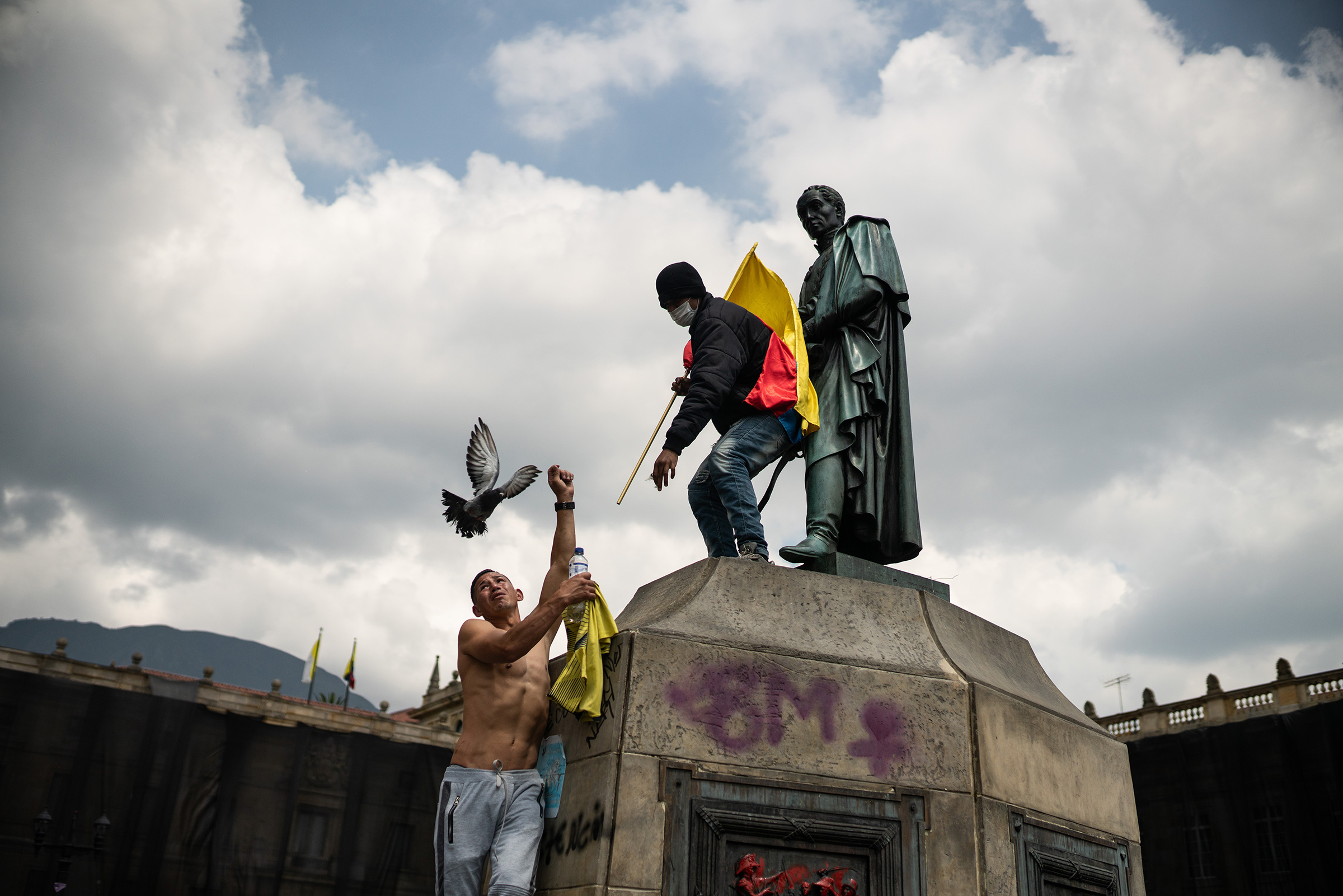 Protesters climb on the statue of Simón Bolívar, the South American independence leader and former president of Colombia, as thousands of Colombians take to the streets to protest against the government's tax reform in Bogotá on May 1.