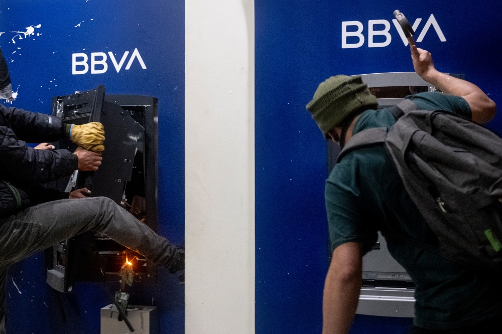 Protesters destroy BBVA bank ATMs amid protests at night. Picture by Santiago Mesa.