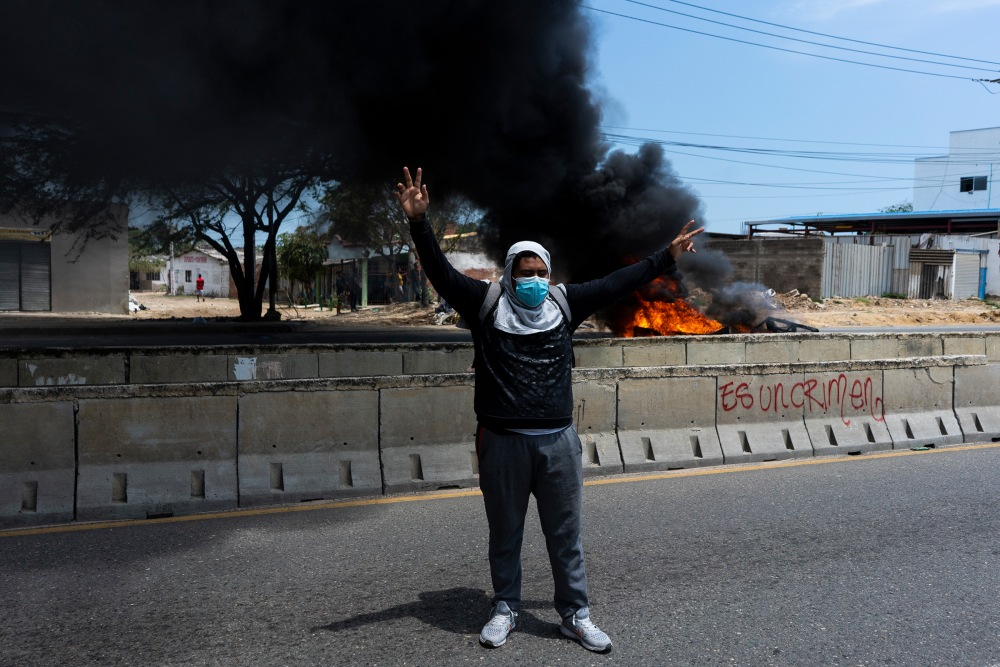 May 1, 2021 - Barranquilla, Colombia. A protester raises his hands in the midst of clashes with the police on Circunvalar Avenue Picture by: Charlie Cordero