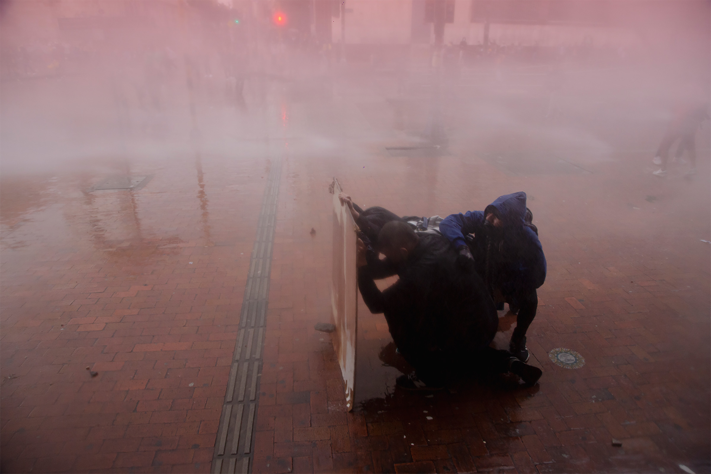 Riot police vehicles fire a water cannon to disperse the protesters in Bogotá on May 5.