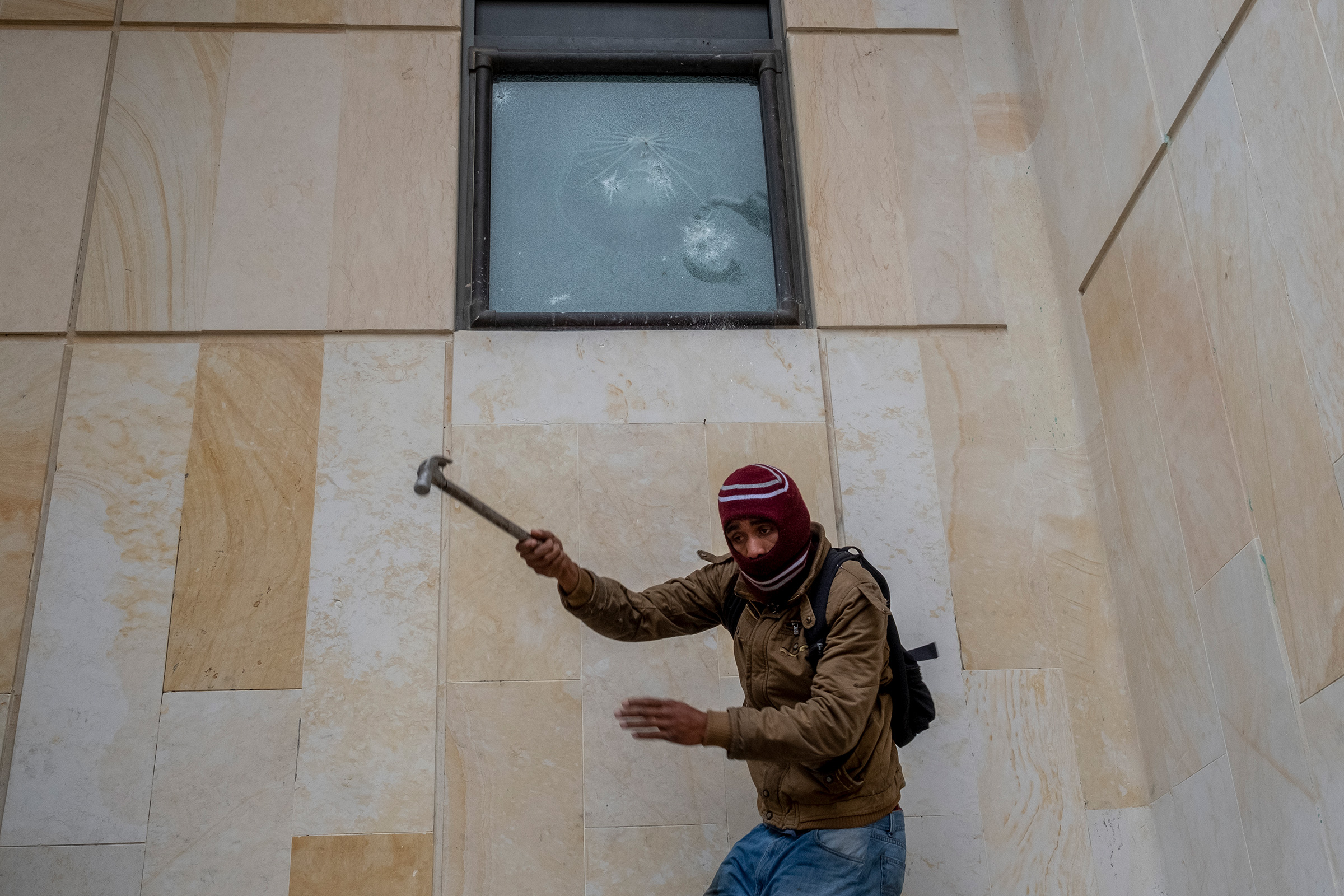 A protestor breaks a window at the Supreme Court Of Justice in downtown Bogotá on April 28.