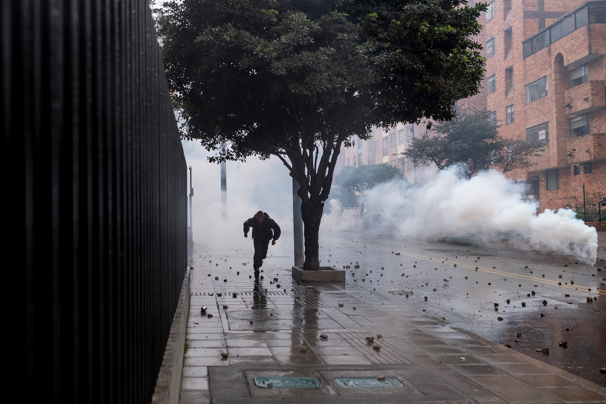 A protester flees tear gas used by the police in northern Bogotá on May 1.