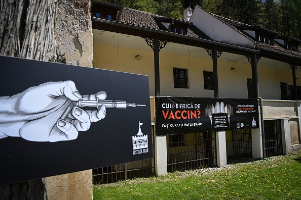 A banner reading  Who's afraid of the vaccine?  in Romanian and depicting syringes as vampire fangs advertises the vaccination marathon organized at  Bran Castle  in Bran village in the central Transylvania region of Romania on May 8, 2021.