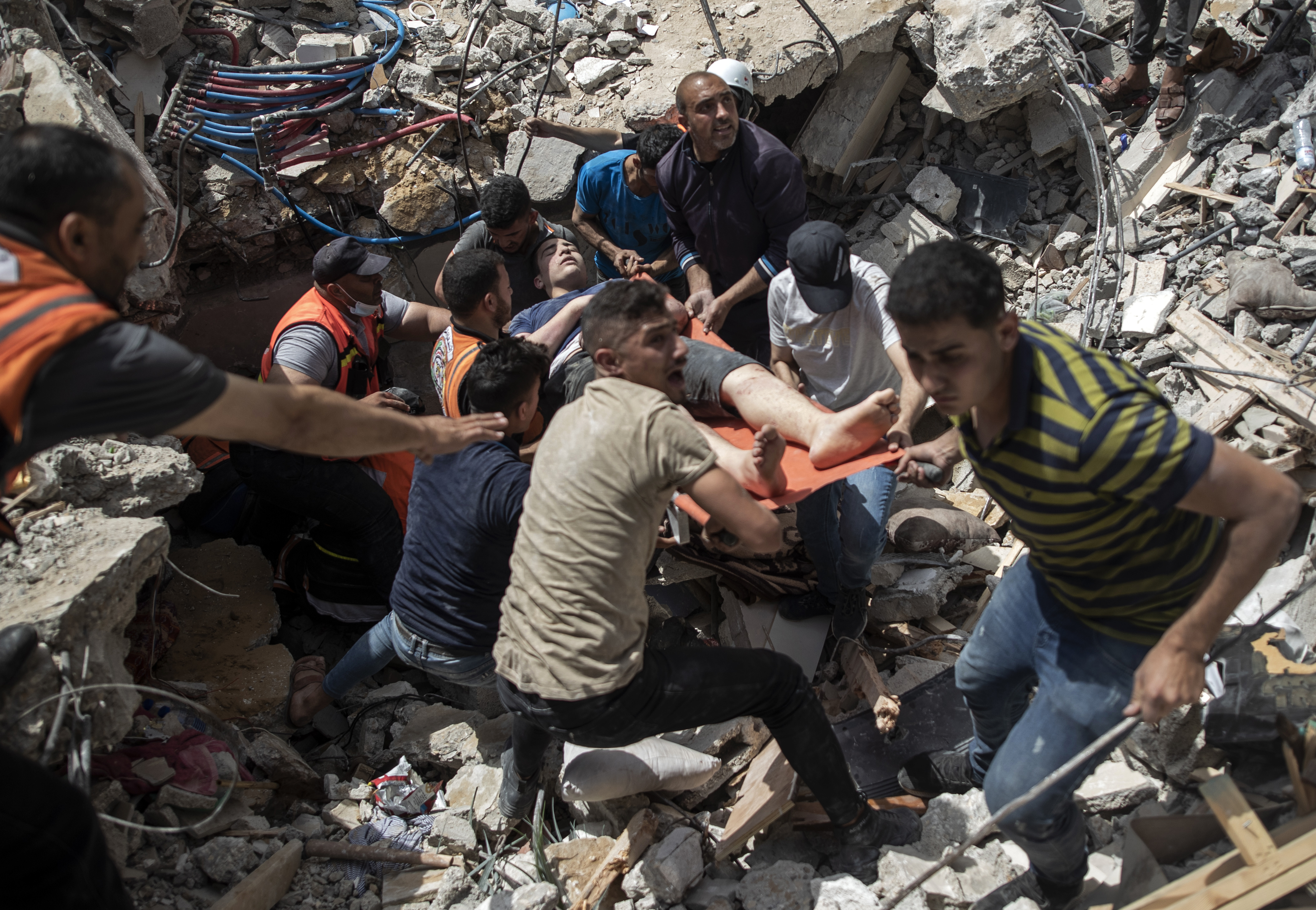 Palestinian rescue a survivor from under the rubble of a destroyed residential building following deadly Israeli airstrikes in Gaza City, on May 16, 2021.