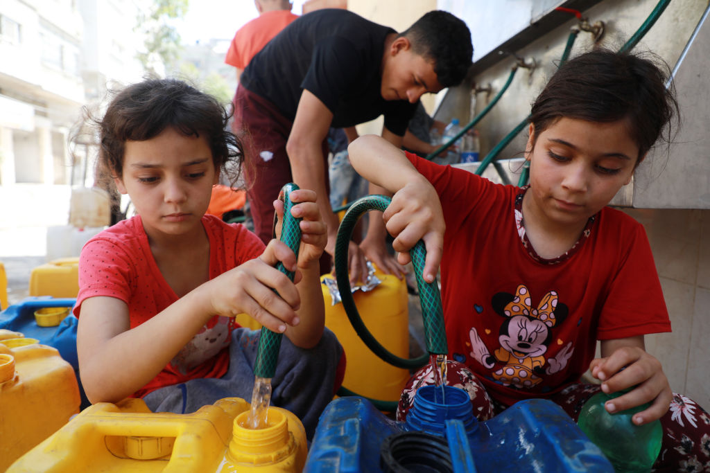 Palestinian children fill up containers with water in Gaza City on May 20, 2021 during the conflict between Israel and Hamas.