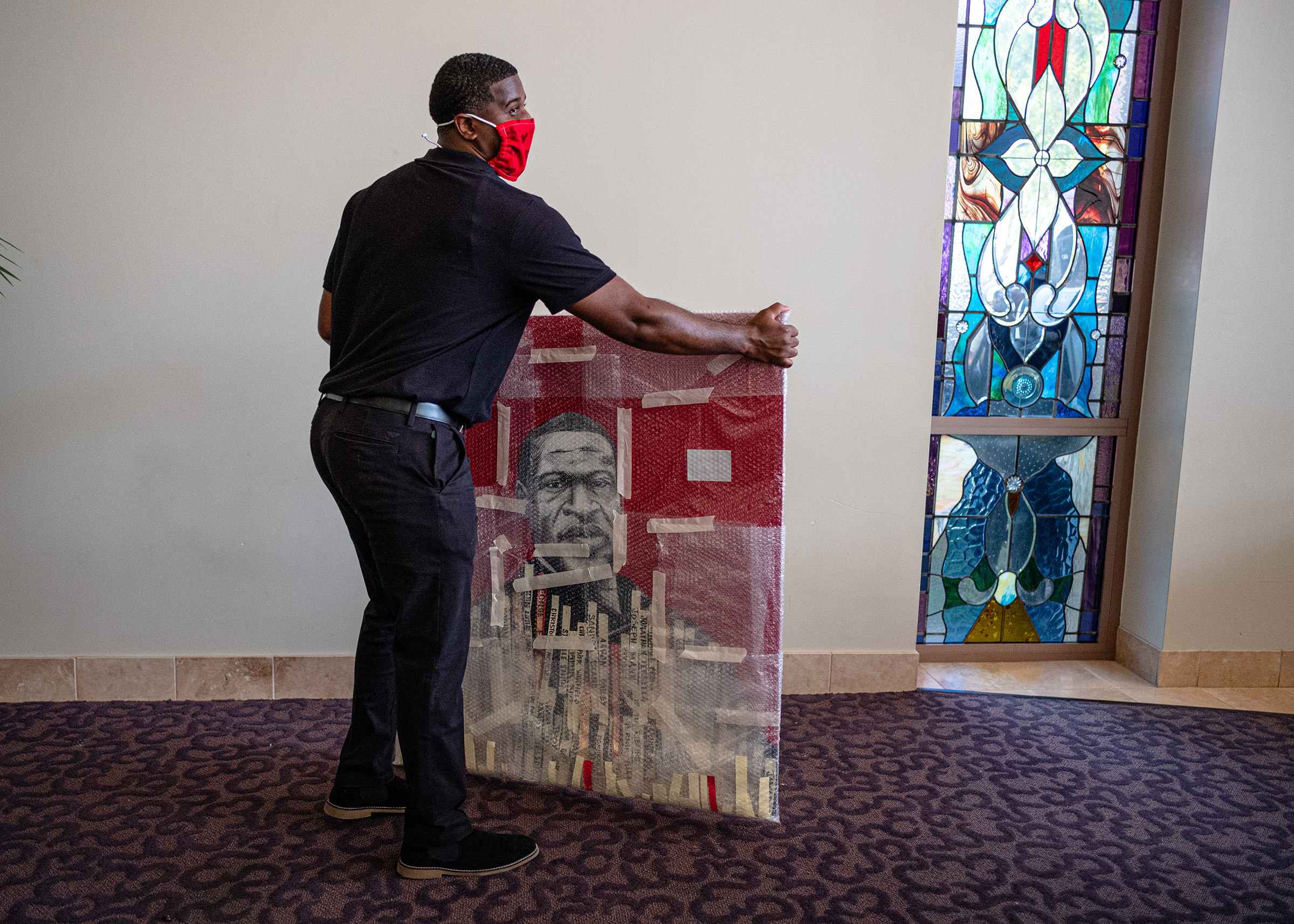 A man moves a painting of George Floyd at the funeral in Houston.
