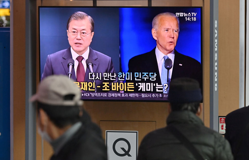 People watch a television news programme reporting on the US presidential election showing images of US President-elect Joe Biden (R) and South Korean President Moon Jae-in (L), at a railway station in Seoul on November 9, 2020.