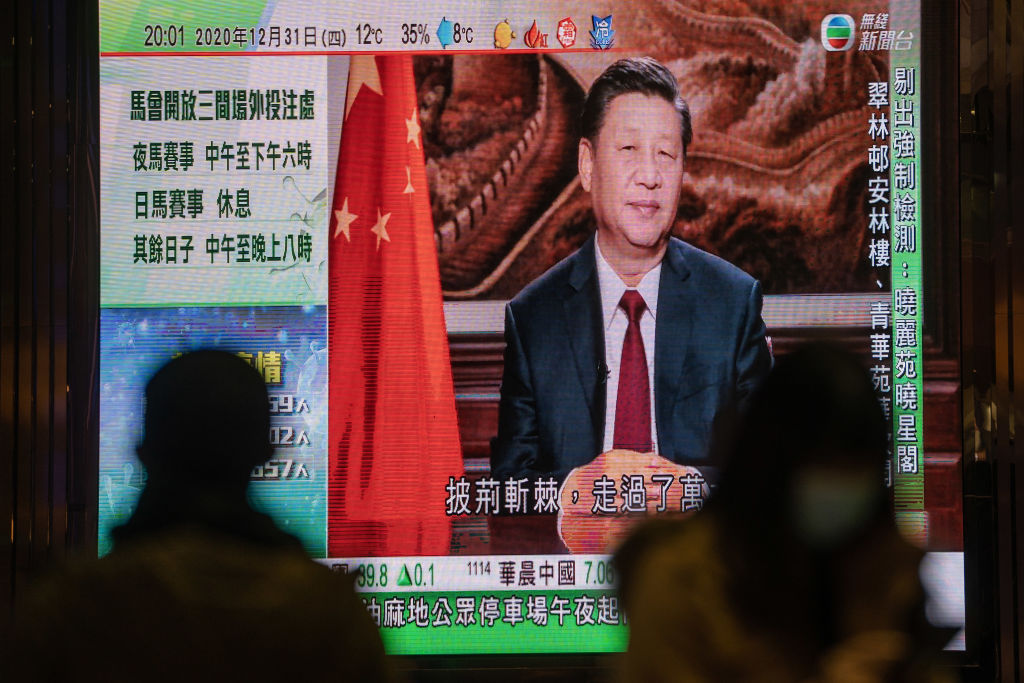 A news report on Chinese President Xi Jinping's New Year's Eve speech is shown on a public screen in Hong Kong, China, on Thursday, Dec. 31, 2020.