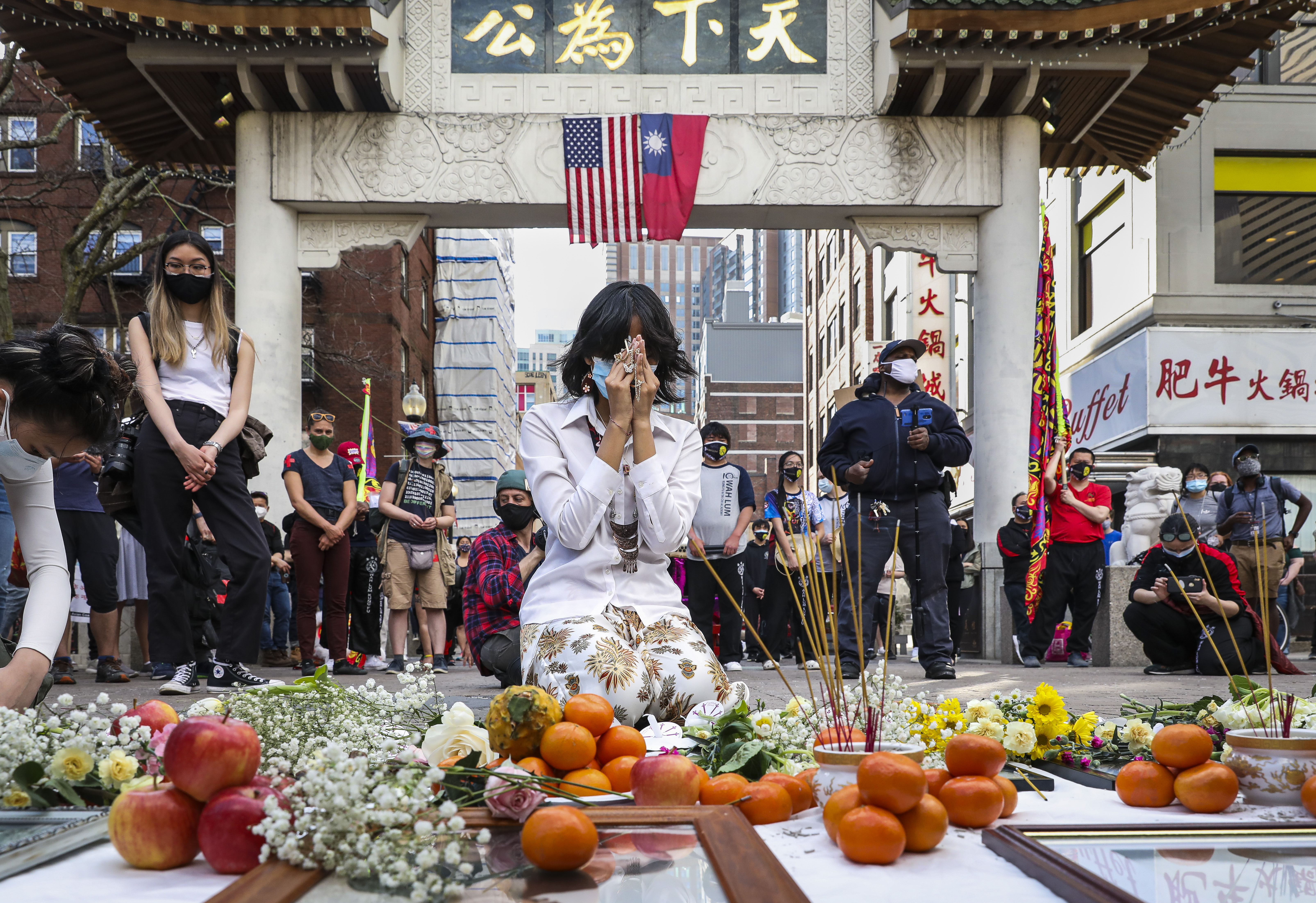Fiona Phie in a moment of silence  after placing an offering among flowers, candles, and incense while honoring victims of anti-Asian hate, on April 10, 2021 in Boston.