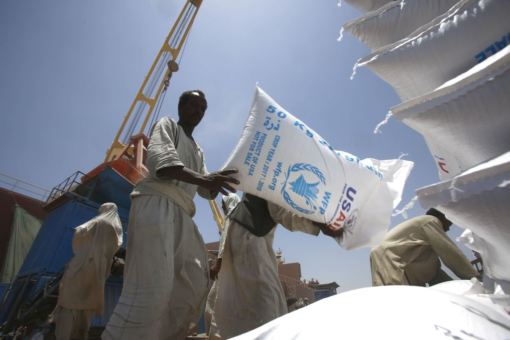 Sudanese dockers unload bags of cereal from one of two US ships carrying humanitarian aid supplies provided by the US development agency USAID, at Port Sudan on the red sea coast on June 5, 2018.