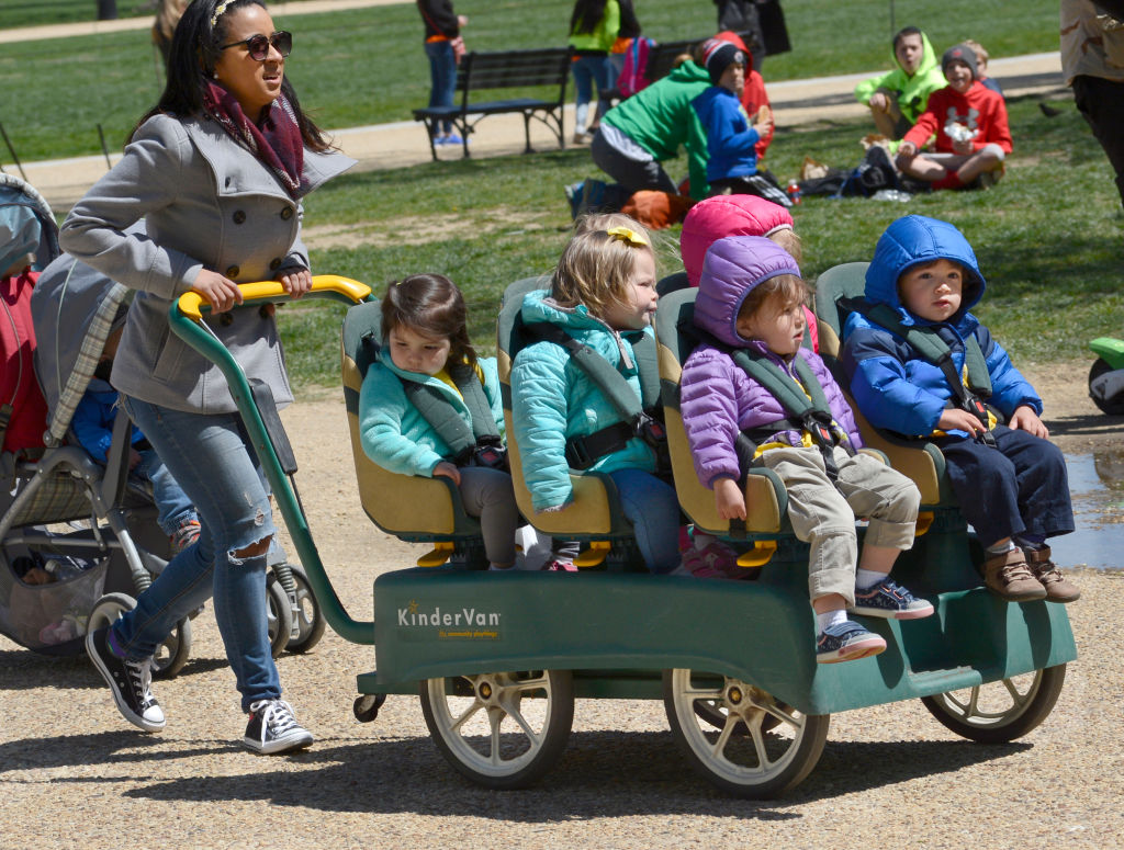WASHINGTON, D.C. - APRIL 20, 2018: A daycare center employee pushes a KinderVan filled with preschool children on an outing along the National Mall in Washington, D.C.
