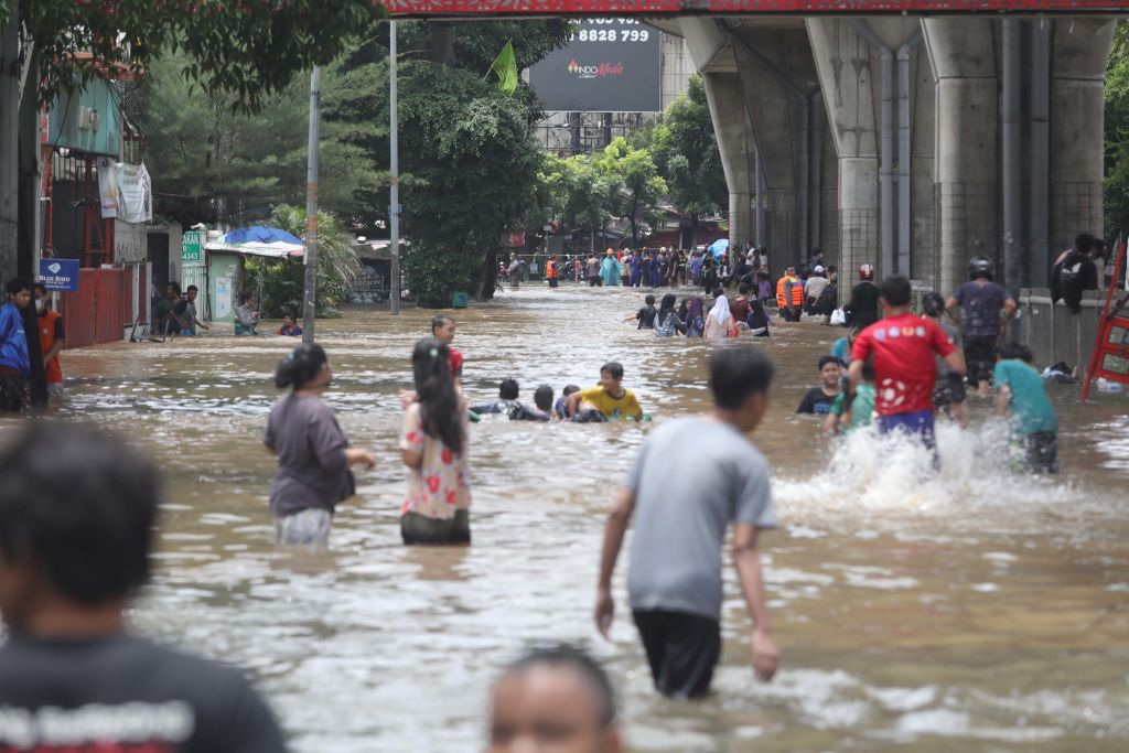 Residents wade through a flooded road in a neighbourhood in Jakarta, Indonesia, on February 20, 2021.