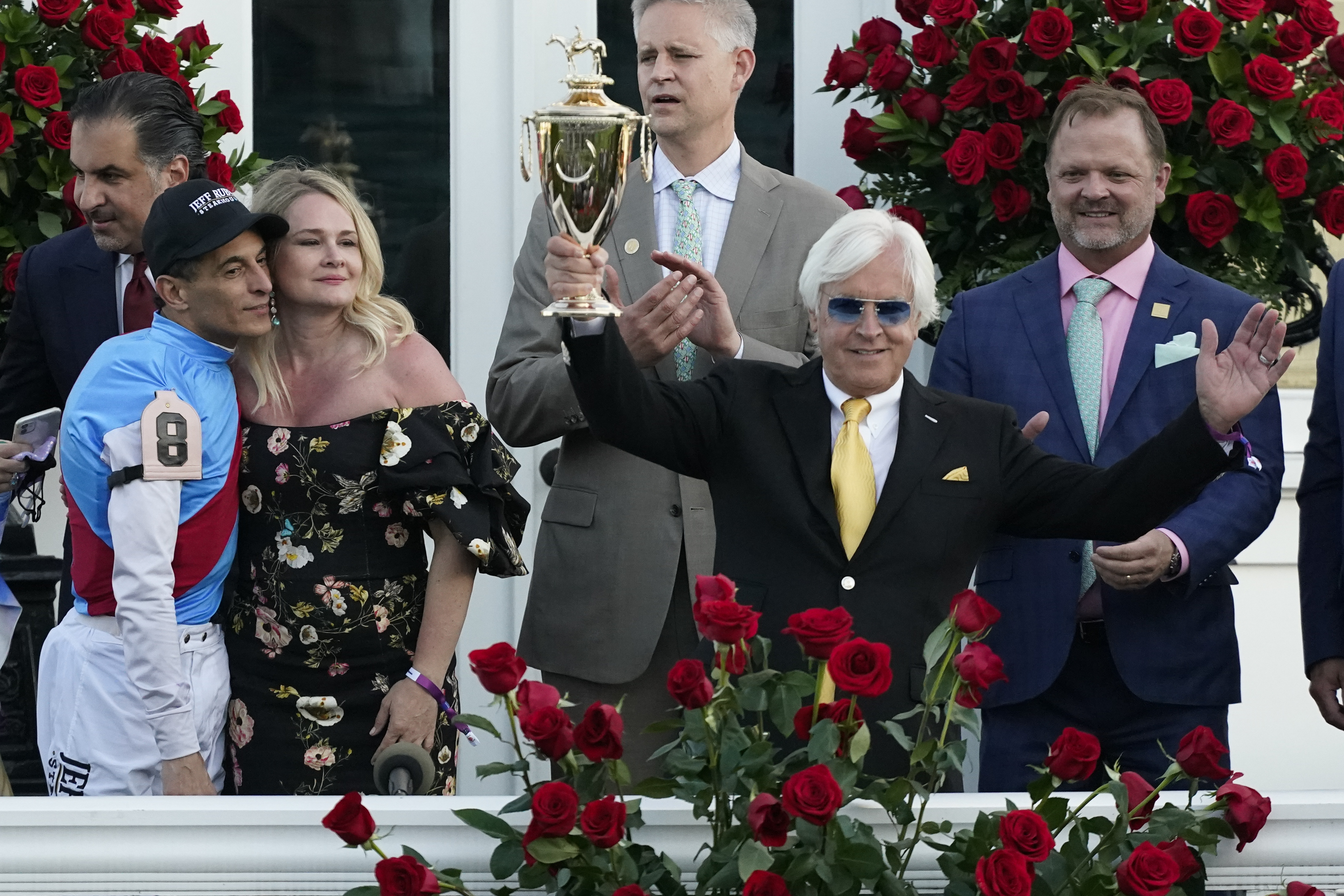 Jockey John Velazquez, left, watches as trainer Bob Baffert holds up the winner's trophy after they victory with Medina Spirit in the 147th running of the Kentucky Derby at Churchill Downs in Louisville, Ky, on May 1, 2021.