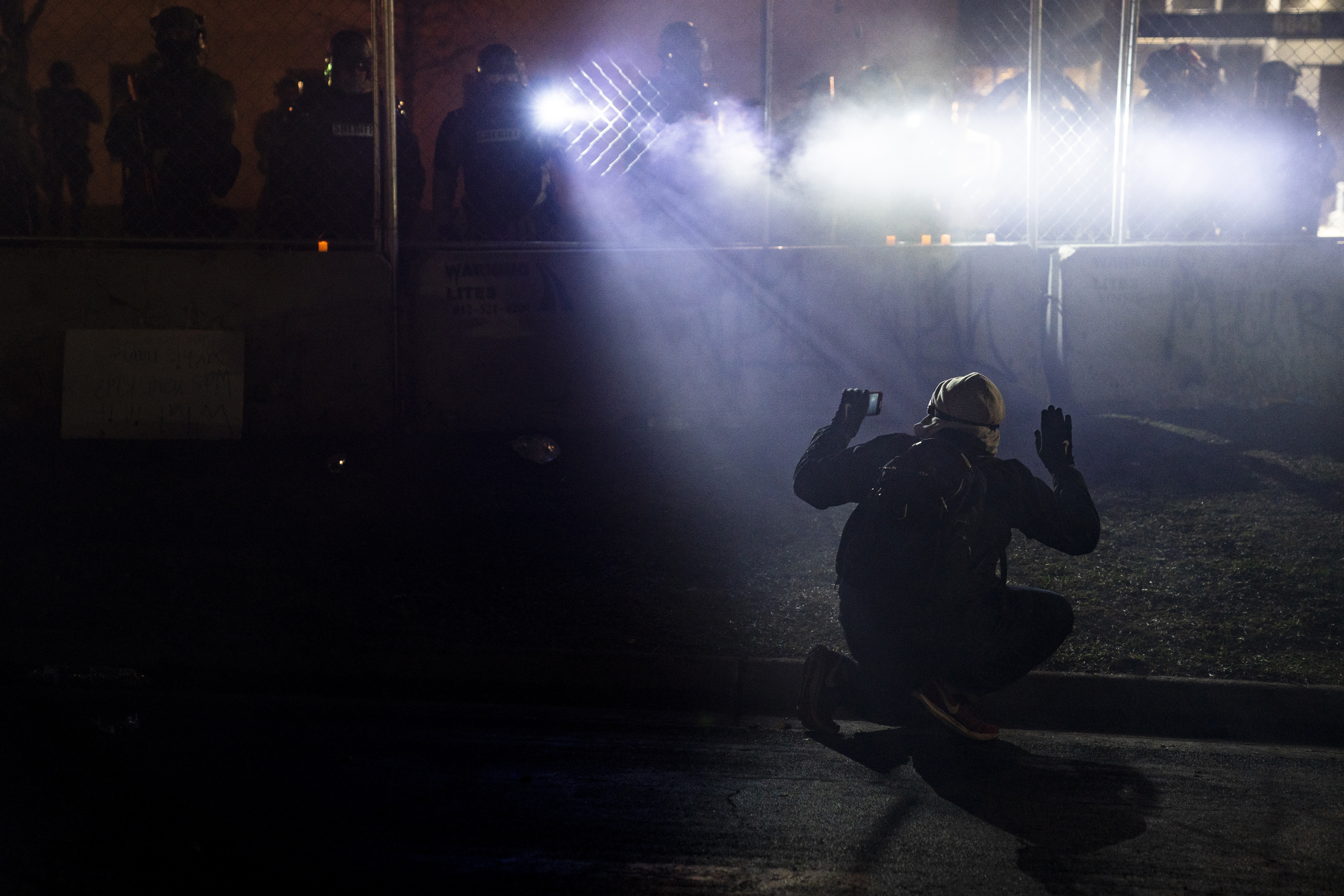 Police shine lights on a demonstrator with raised hands during a protest outside the Brooklyn Center Police Department on in Brooklyn Center, Minn., on this April 14, 2021.