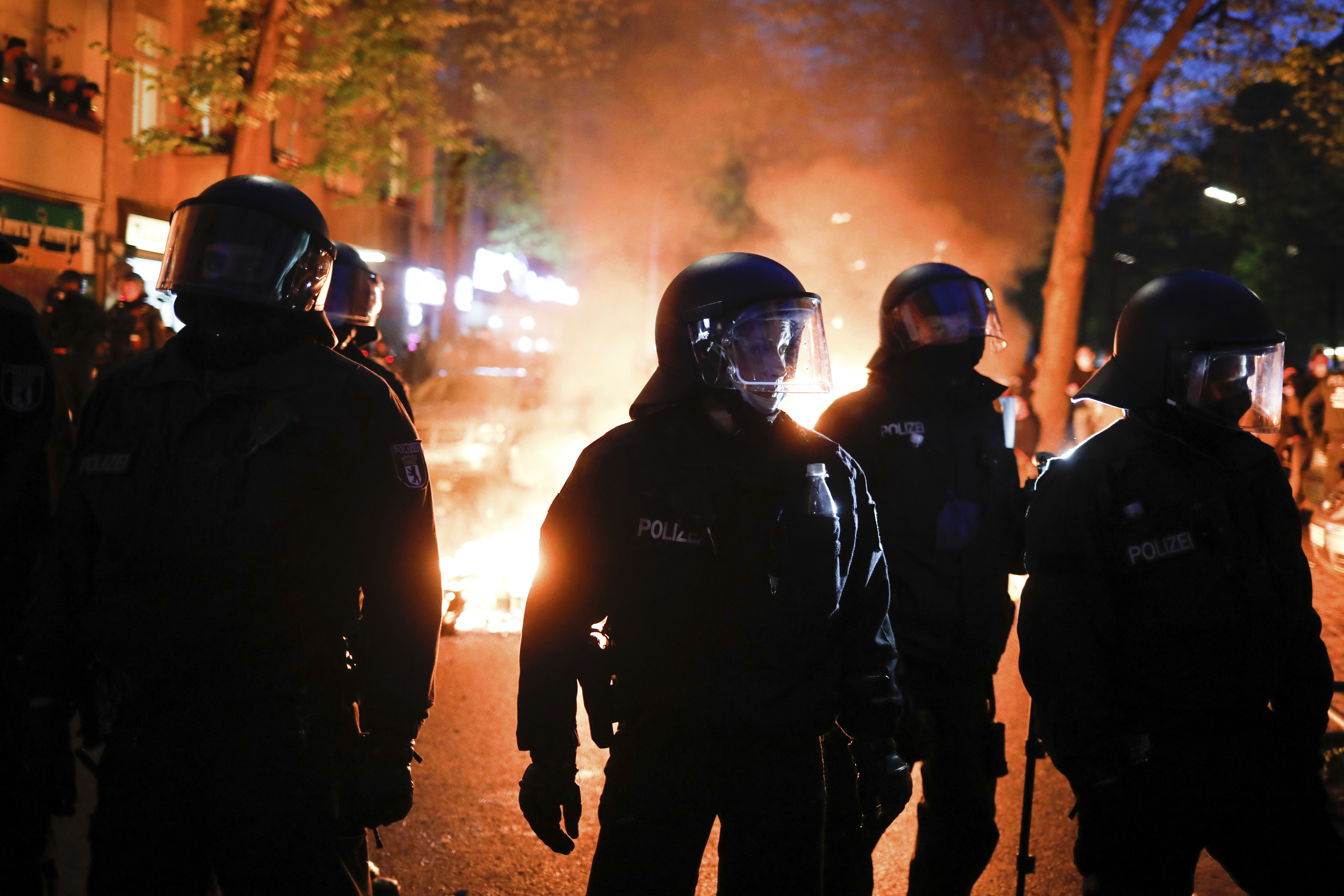 Police officers stand in front of a fire set up by demonstrators during a May Day rally in Berlin, Germany on May 1, 2021.
