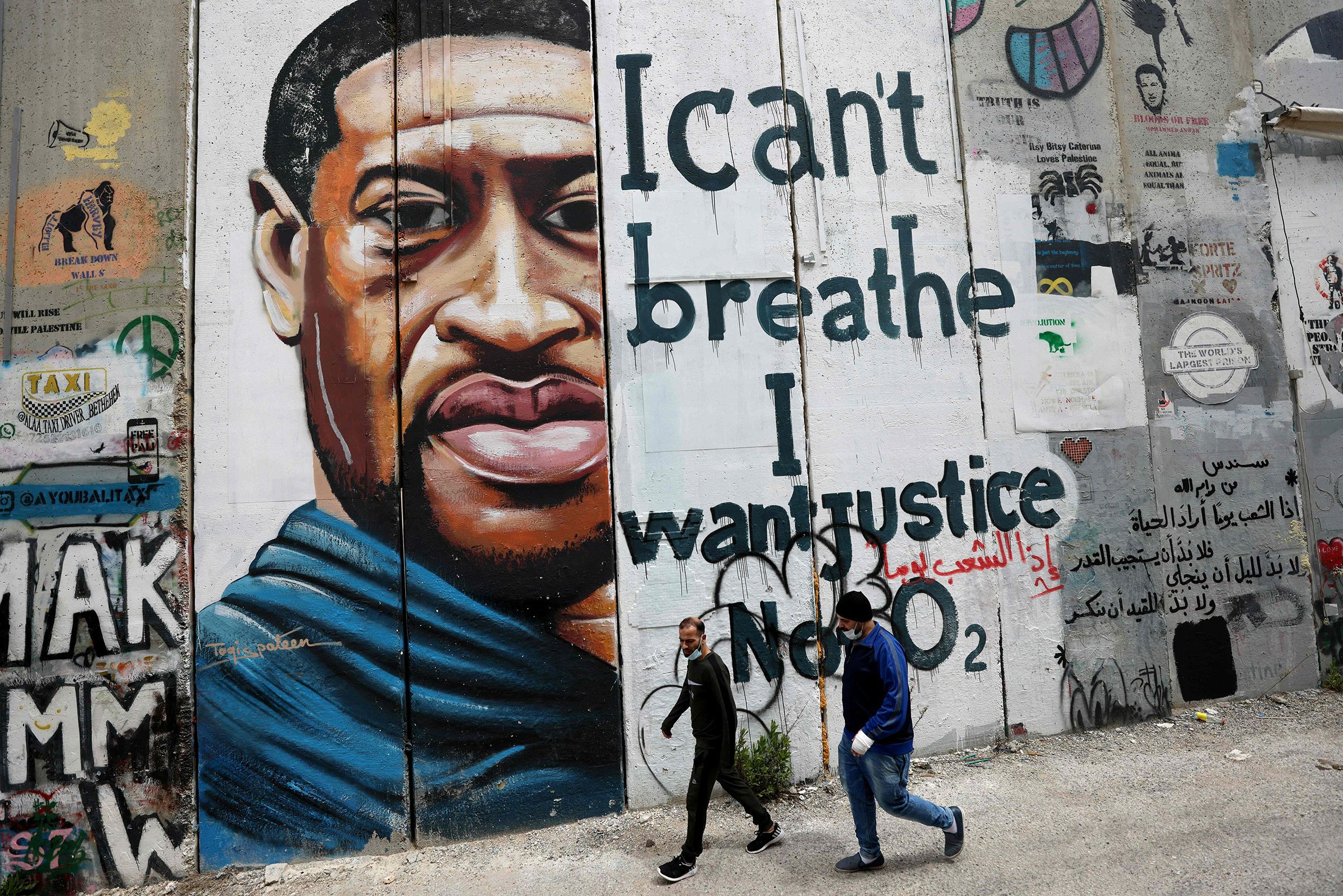 People walk past a mural showing the face of George Floyd on a section of the wall in Bethlehem on March 31.