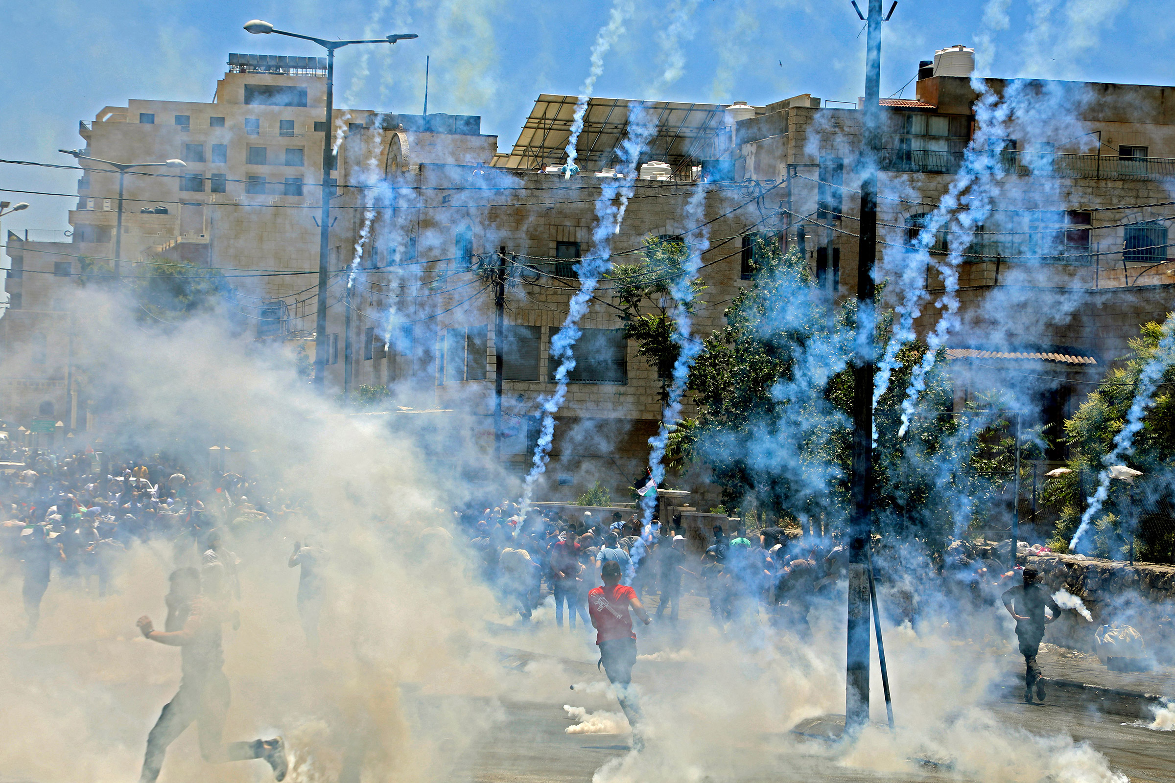 Israeli troops fire tear gas towards demonstrators during a protest against Israeli occupation in the West Bank on May 18.