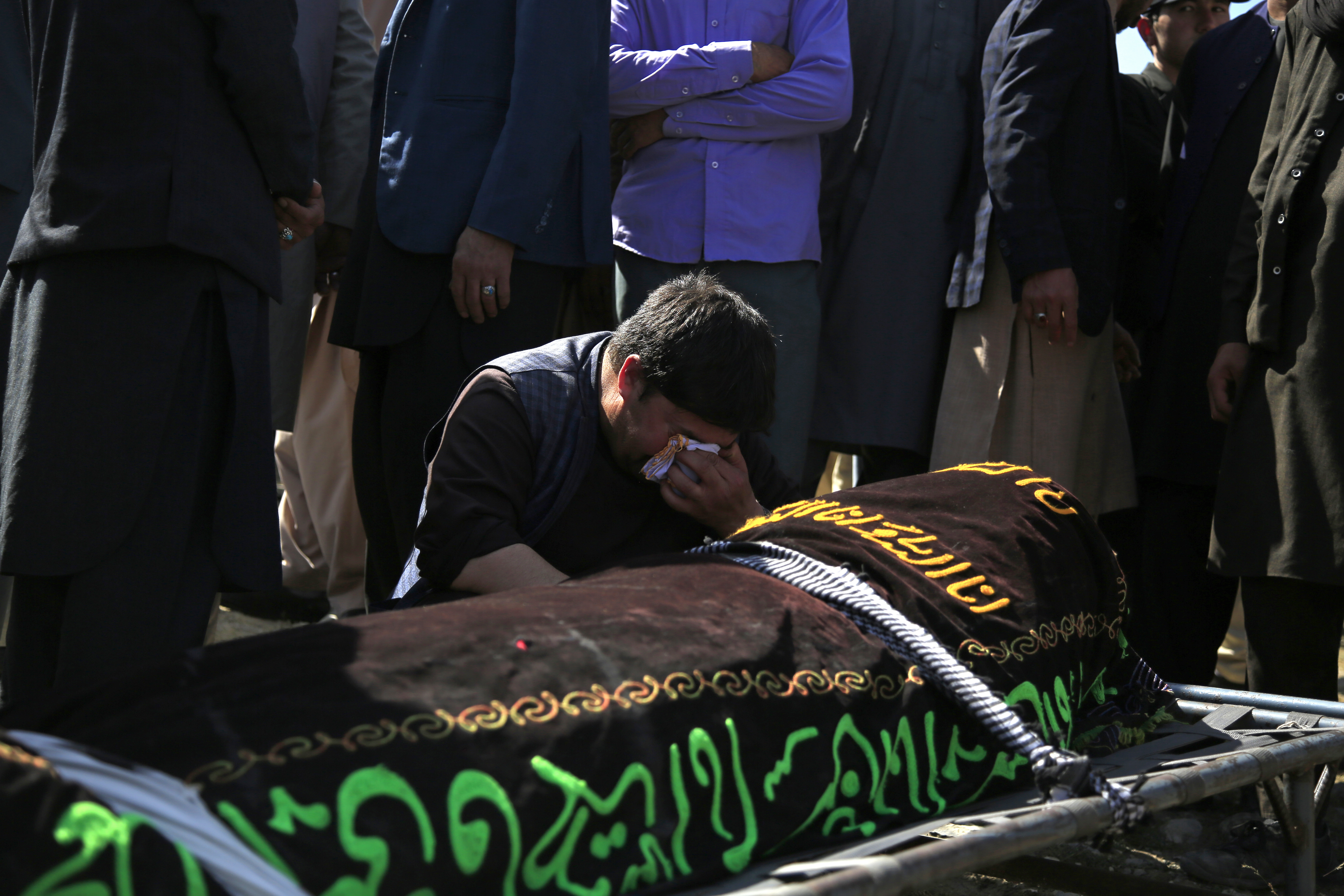 A man cries over the body of a victim of deadly bombings near a school, at a cemetery west of Kabul, Afghanistan, on May 9, 2021.