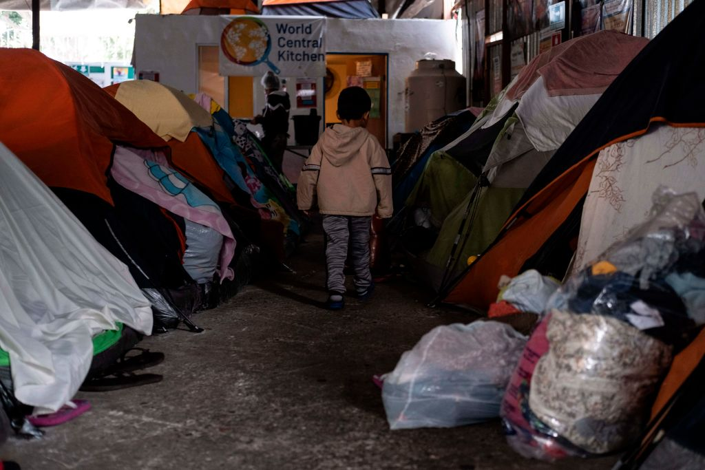 A migrant boy walks amid tents at the Juventud 2000 migrant shelter in Tijuana, Mexico, on December 17, 2020.