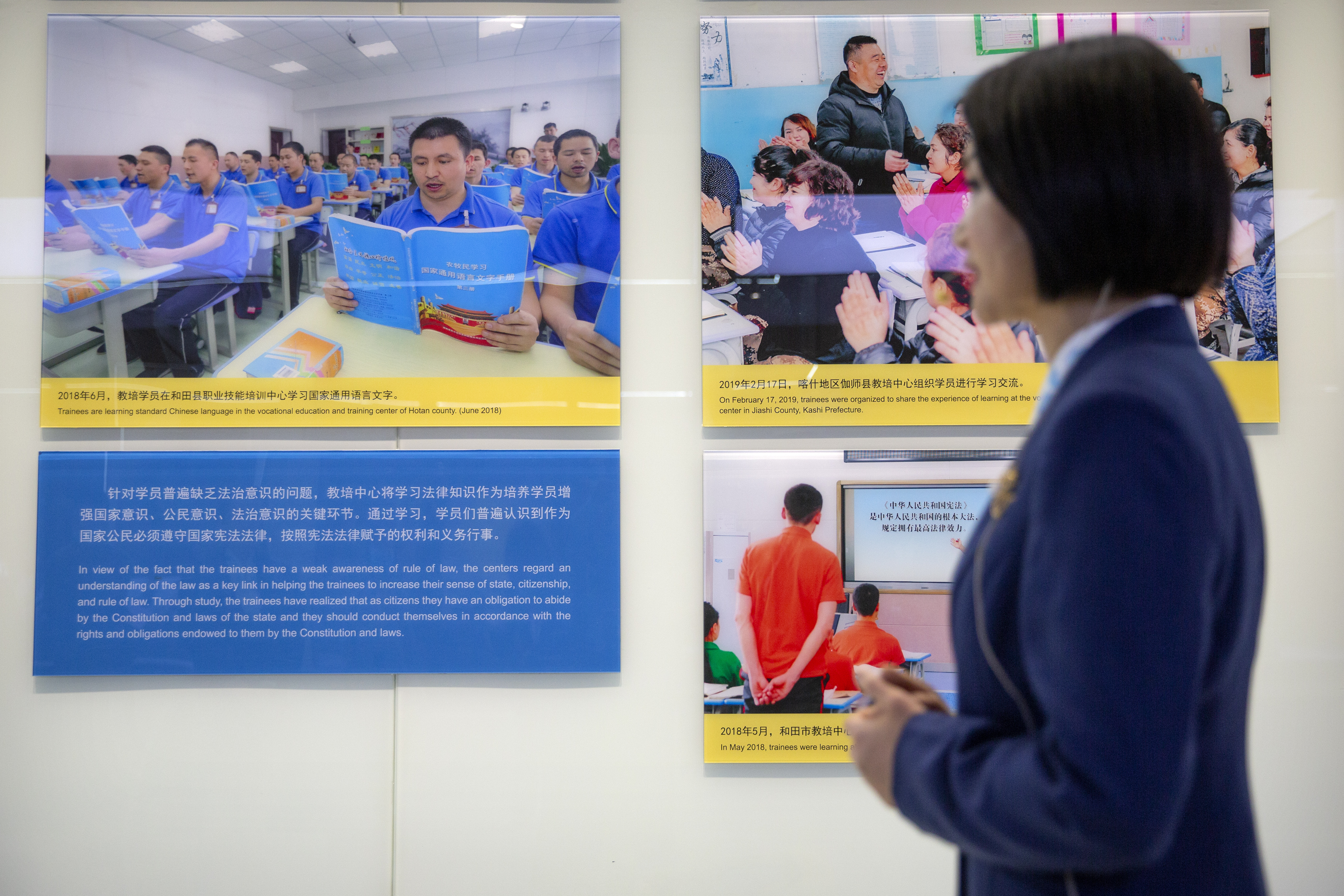 A tour guide stands near a display showing images of people at locations described as vocational training centers in southern Xinjiang at the Exhibition of the Fight Against Terrorism and Extremism in Urumqi in western China's Xinjiang Uyghur Autonomous Region  on April 21, 2021. Human rights groups and Western nations led by the United States, Britain and Germany accused China of massive crimes against the Uyghur minority and demanded unimpeded access for U.N. experts at a virtual meeting on Wednesday, May 12, 2021 denounced by China as  politically motivated  and based on  lies.