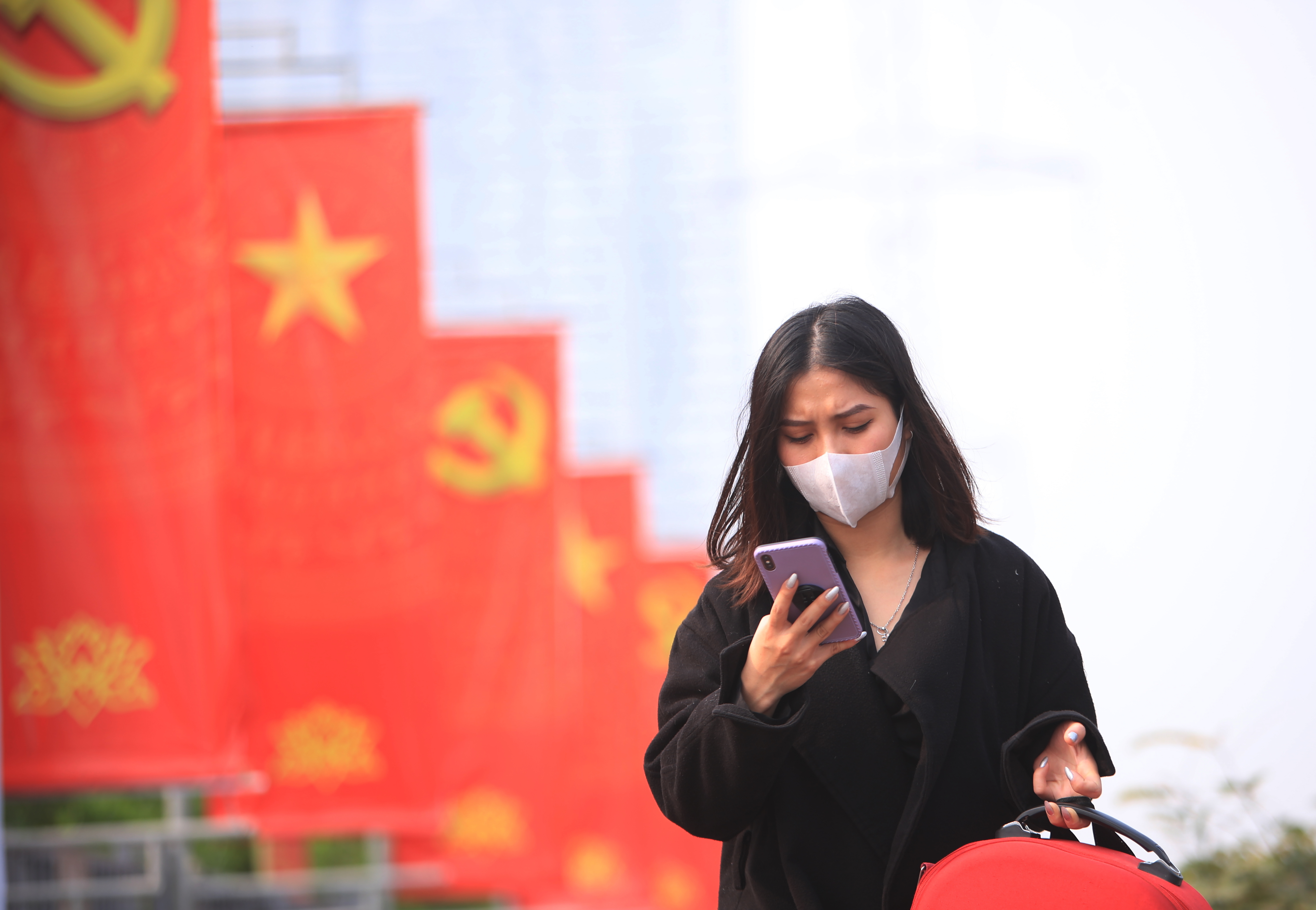 A woman wearing a face mask looks at her phone in Hanoi, Vietnam, on  Jan. 23, 2021.