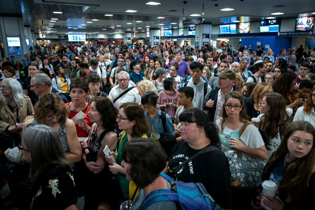 Passengers line up to board a delayed Amtrak train at New York Penn Station, June 19, 2019 in New York City.