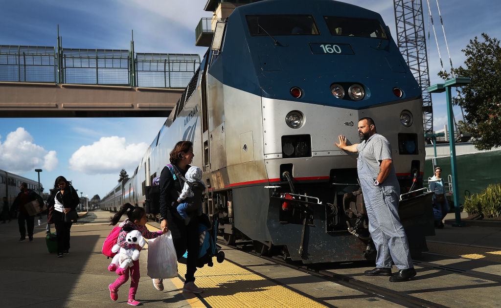 An Amtrak engineer leans on the locomotive as passengers disembark from Amtrak's California Zephyr at the end of its daily 2,438-mile trip to Emeryville/San Francisco from Chicago that took roughly 52 hours on March 25, 2017 in Emeryville, California.