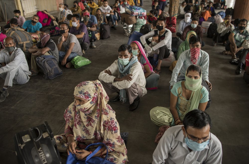 Migrant workers sit at a bus terminal as they wait to catch state-provided transportation to their home villages, in Greater Noida, Uttar Pradesh, on May 29, 2020. Migrant workers, who form part of India's vast informal sector, were the worst hit by the shutdown. Millions lost jobs and incomes.