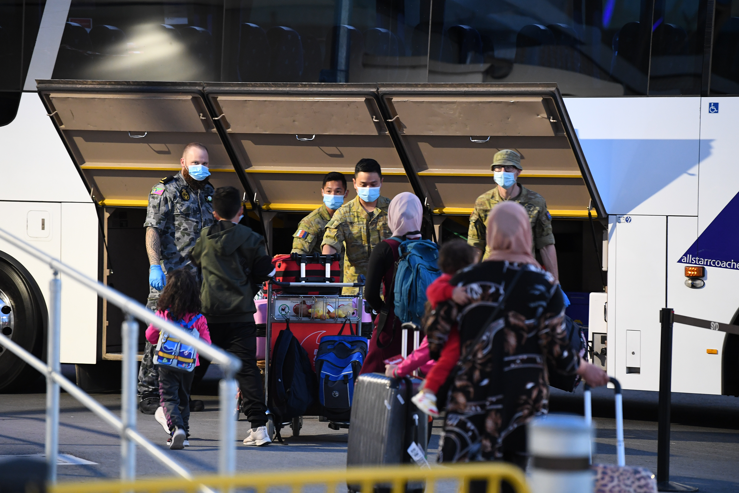 Passengers wearing face masks arrive to Sydney after a Qatar Airways flight on May 1, 2021. Australia banned flights from India earlier this week due to the escalating COVID-19 outbreak in India, but stranded Australians were still able to return on flights by transiting through Doha.