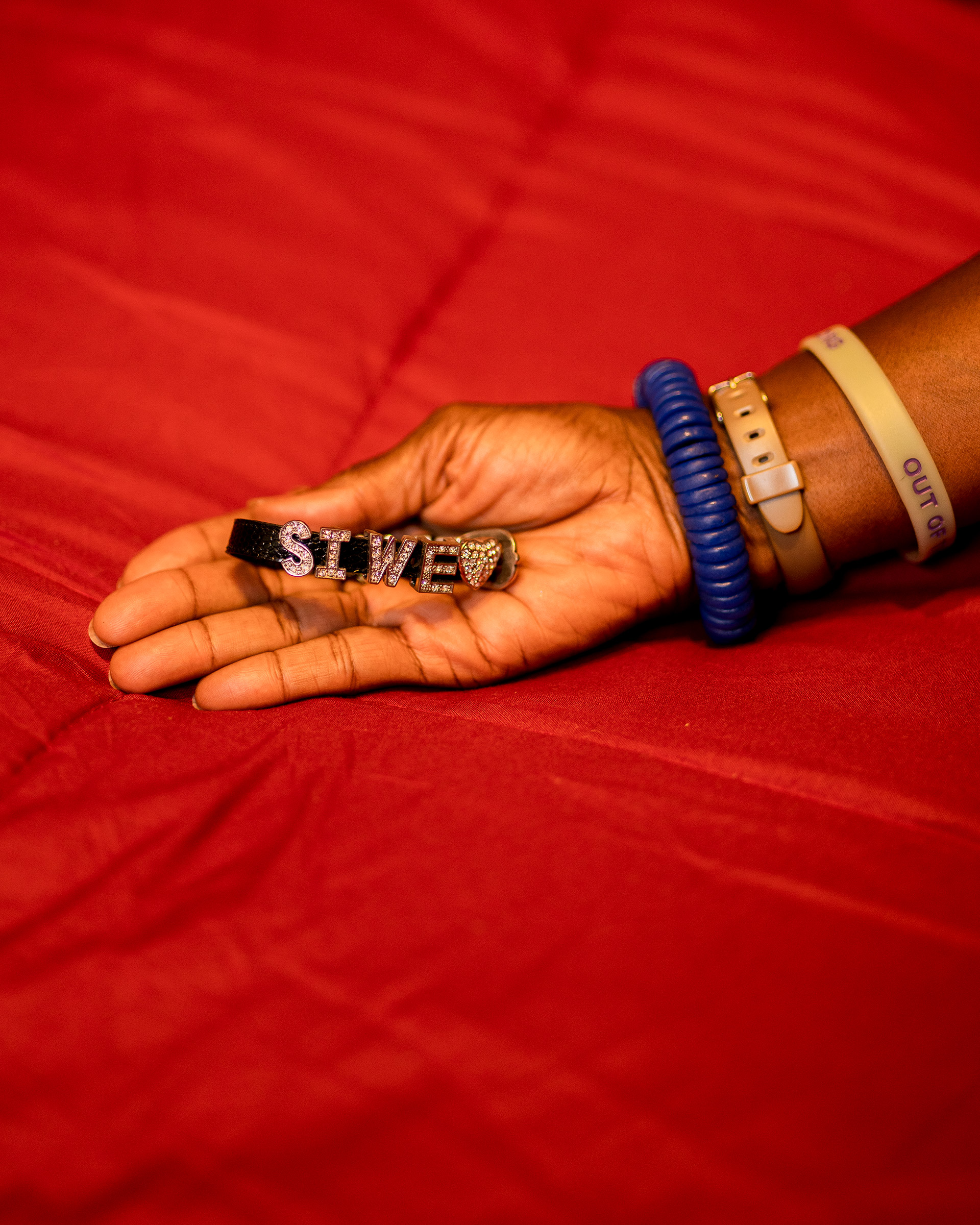 """Dionne Monsanto holds a bracelet that Siwe made. """"With a name like Busisiwe Ayo Monsanto...she could never buy anything pre-made with her name. So it was a big deal that there was a place that she could do that,"""" Monsanto says."""