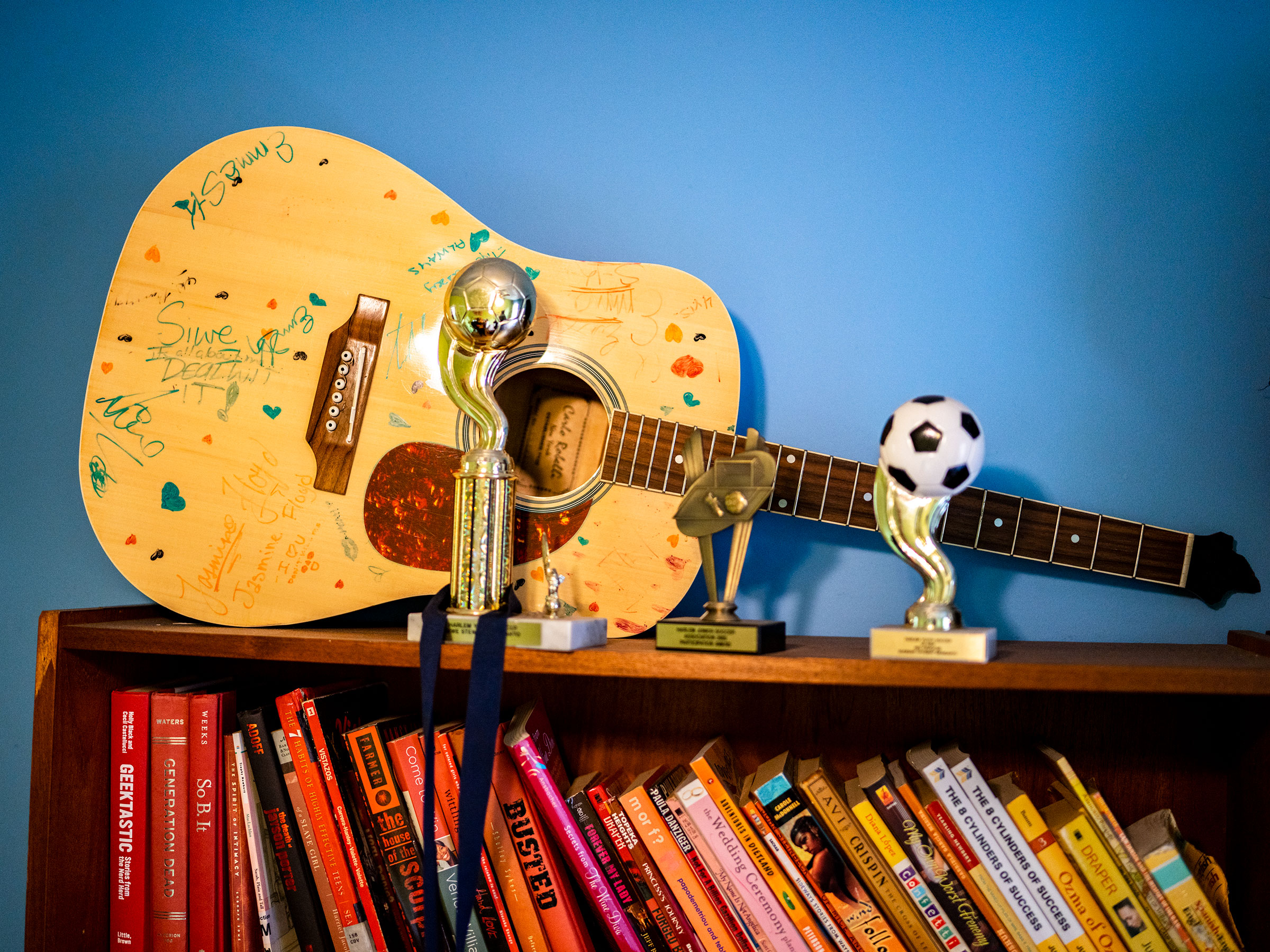 """A guitar amongst trophies and books on a shelf in Siwe's bedroom. """"She was brilliant,  her mother said.  She was beautiful. She was a writer. She was a guitar player. She was a dancer."""