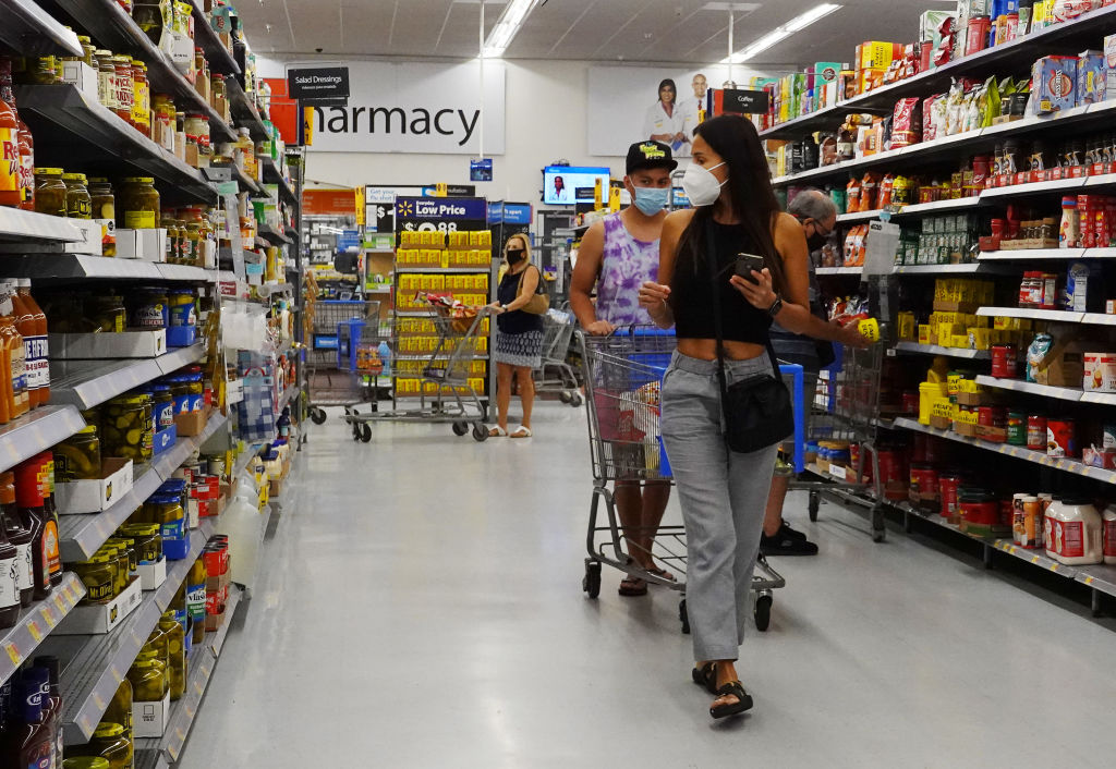 People wearing protective masks shop in a Walmart store on May 18, 2021 in Hallandale Beach, Florida. Walmart announced that customers who are fully vaccinated against Covid-19 will not need to wear a mask in its stores, unless one is required by state or local laws. The announcement came after the Centers for Disease Control and Prevention said that fully vaccinated people do not need to wear a mask or stay 6 feet apart from others in most cases, whether indoors or outdoors.
