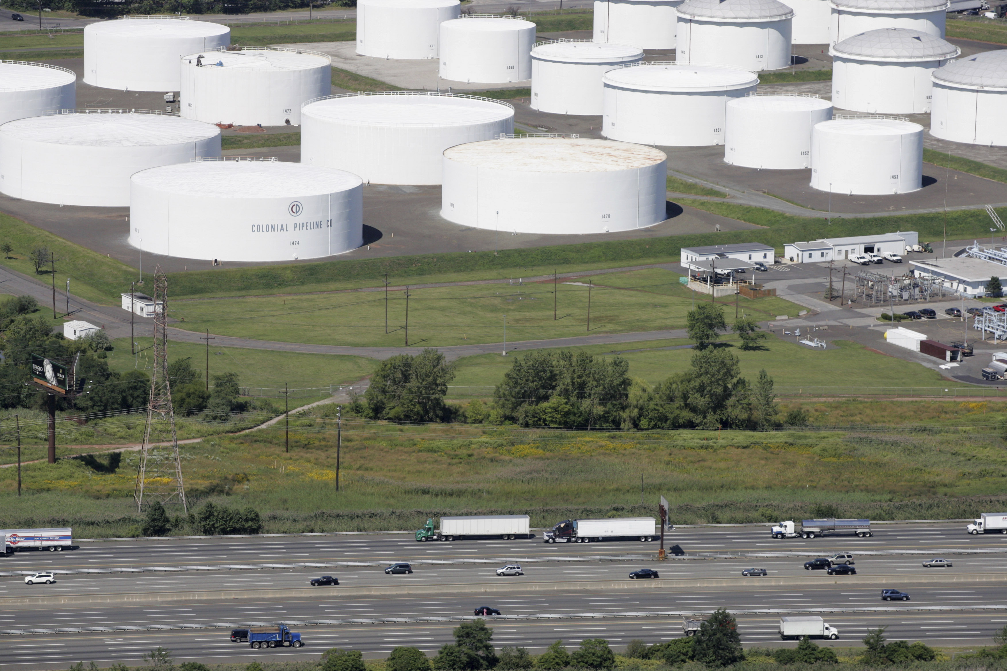In this Sept. 8, 2008 file photo traffic on I-95 passes oil storage tanks owned by the Colonial Pipeline Company in Linden, N.J. A major pipeline that transports fuels along the East Coast says it had to stop operations because it was the victim of a cyberattack.