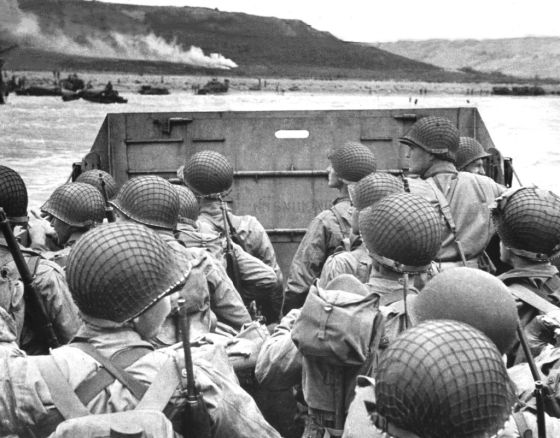 American shock troops huddle behind the protective front of a landing craft as it nears the beachhead on the Normandy coast of France