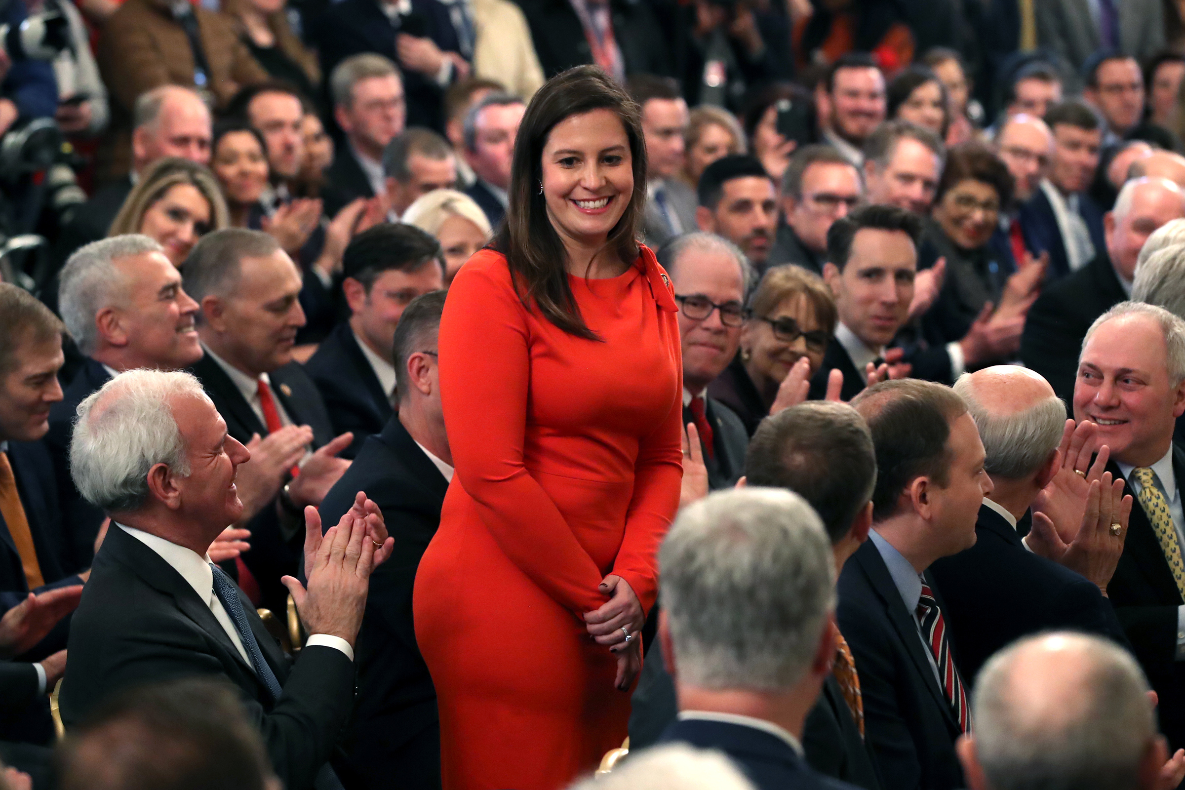 Elise Stefanik stands as she's acknowledged by former President Donald Trump as he speaks one day after the U.S. Senate acquitted him on two articles of impeachment, in the East Room of the White House, Feb. 6, 2020