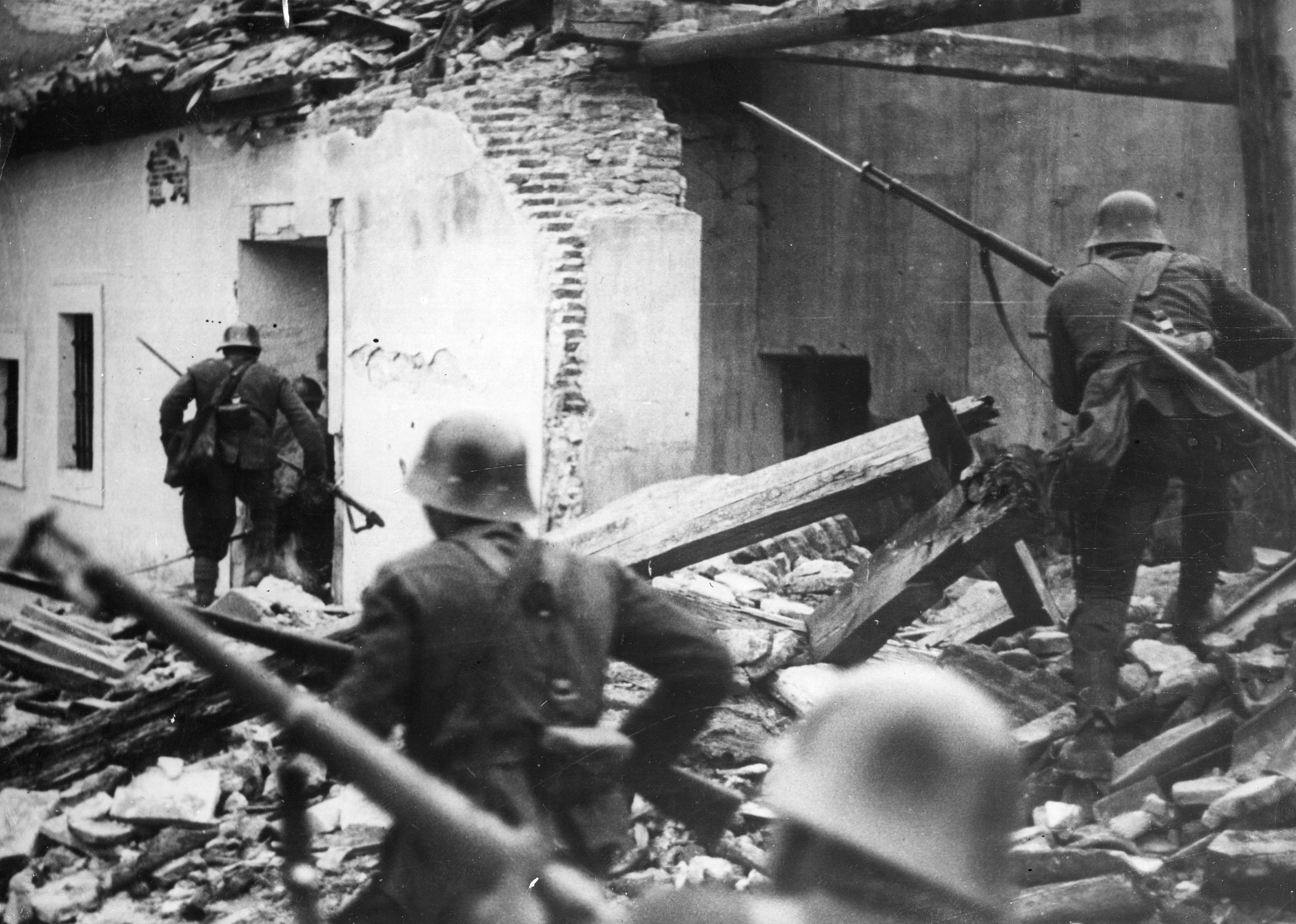 Nationalist troops advance through the debris of houses wrecked in air raids in Madrid, on April 2, 1937.