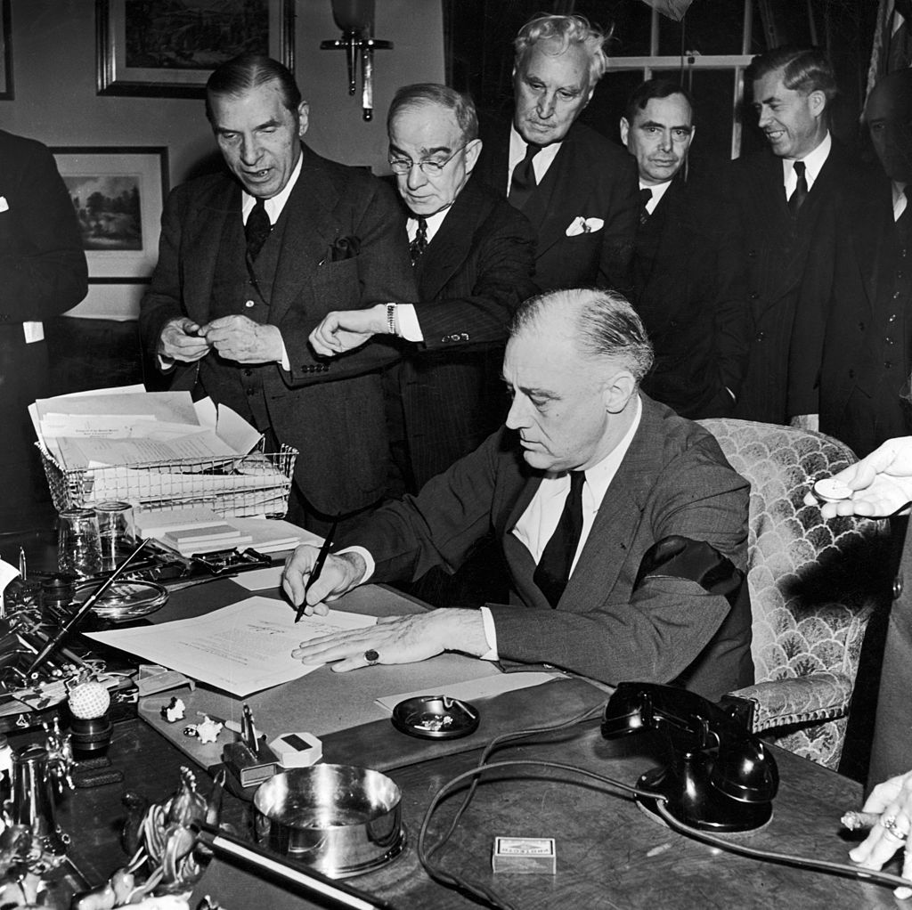President Franklin D. Roosevelt (wearing black armband) signing declaration of war as others look on, following Japanese bombing of Pearl Harbor.