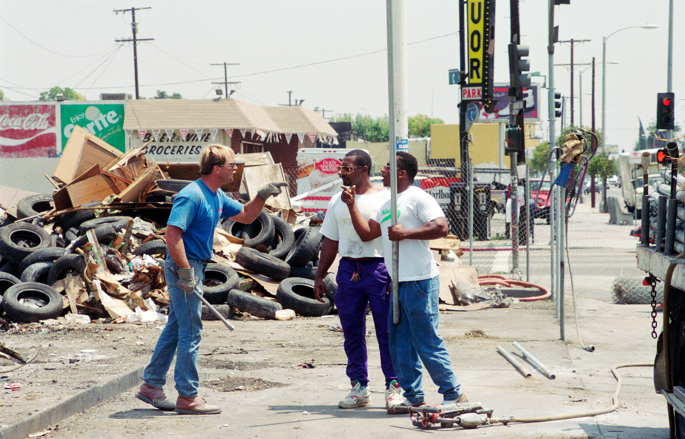 Armed with metal pipes, a construction worker (in blue) and demonstrators threaten one another during a protest on the northwest corner of the intersection of Florence and Normandie on Aug. 4, 1992. The demonstration was about the lack of Black employees on the job site.