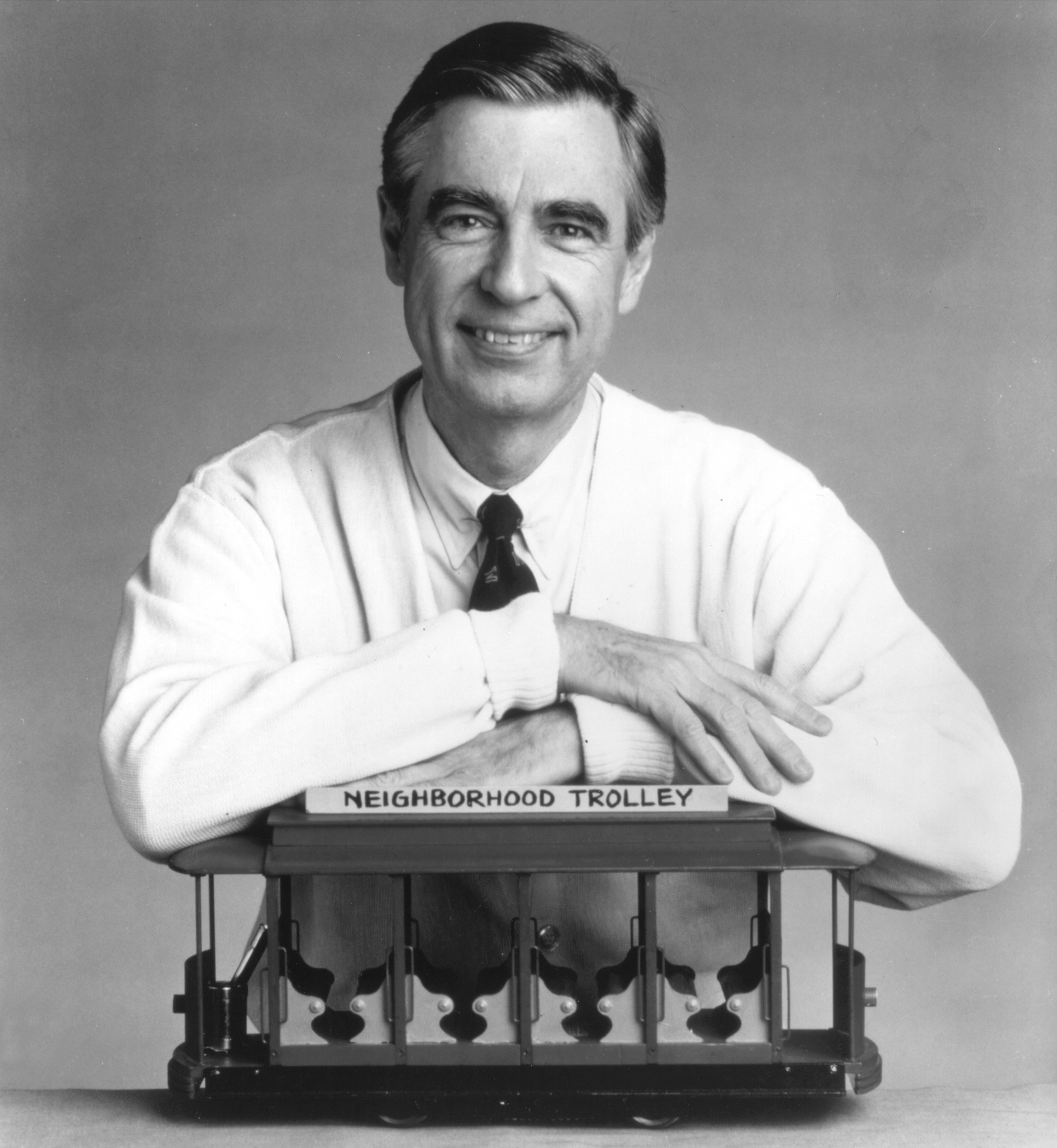 Fred Rogers, the host of the children's television series,  Mr. Rogers' Neighborhood,  rests his arms on a small trolley in this promotional portrait from the 1980's.