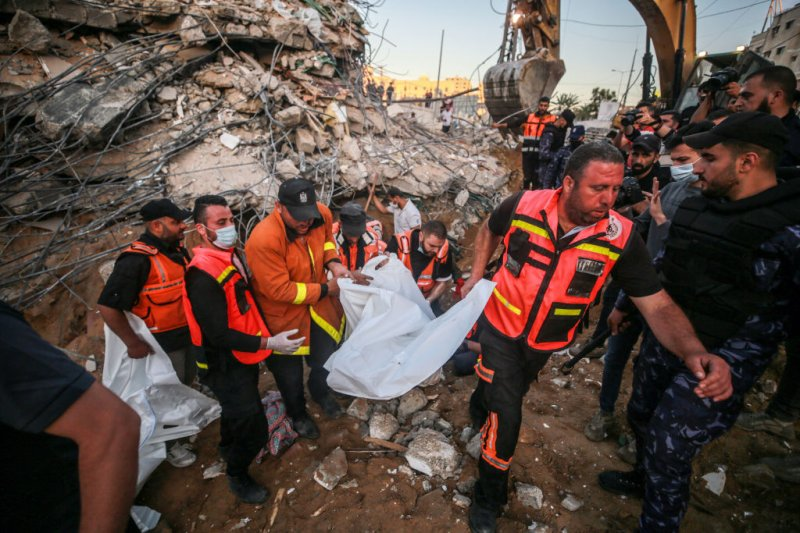 Palestinian civil defense teams take part in rescue works at the rubble of a building belonging to a Palestinian family after Israeli conducted airstrikes in Beit Lahia, Gaza on May 13, 2021.